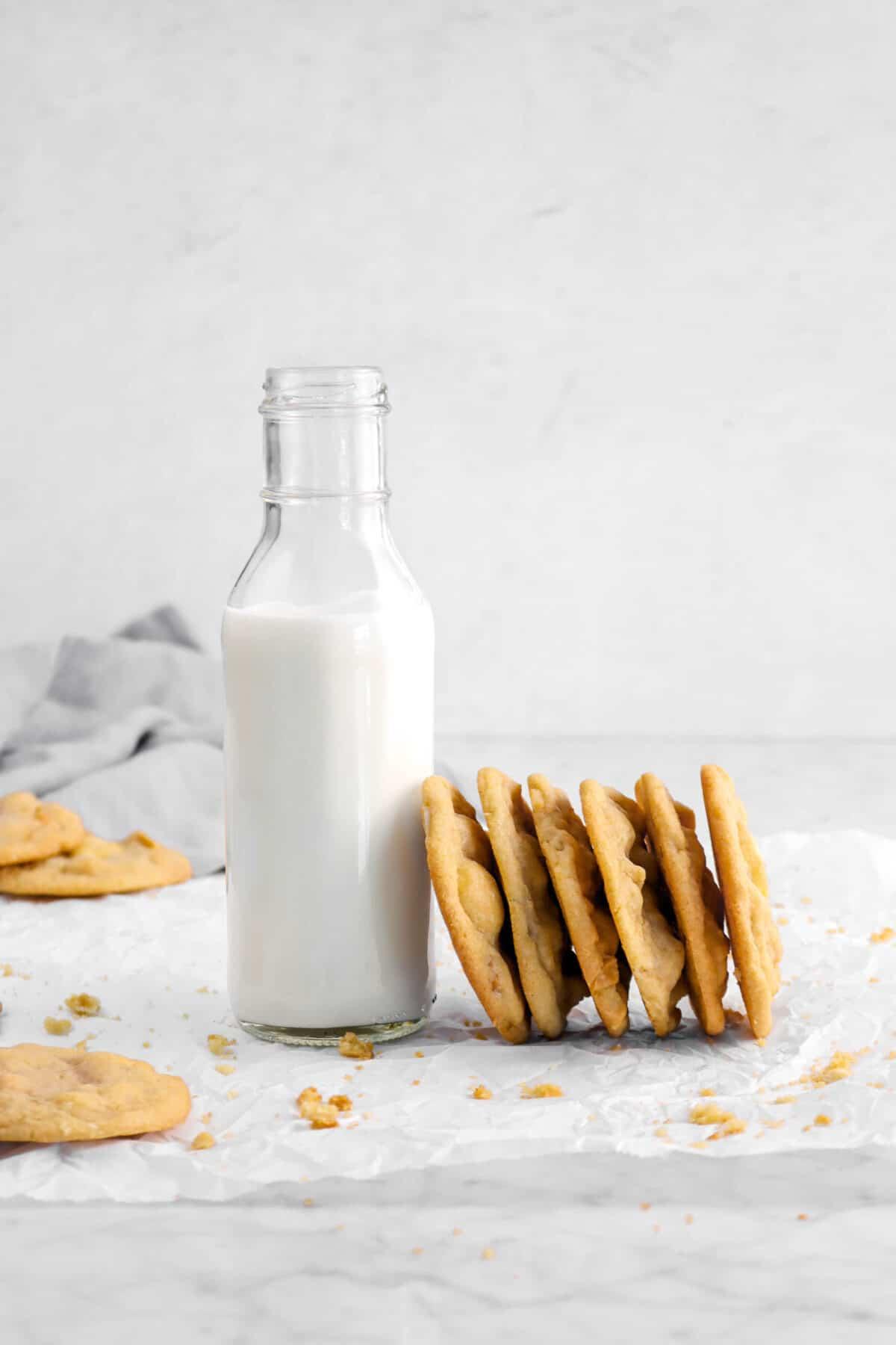 white chocolate macadamia nut cookies leaning against jar of milk