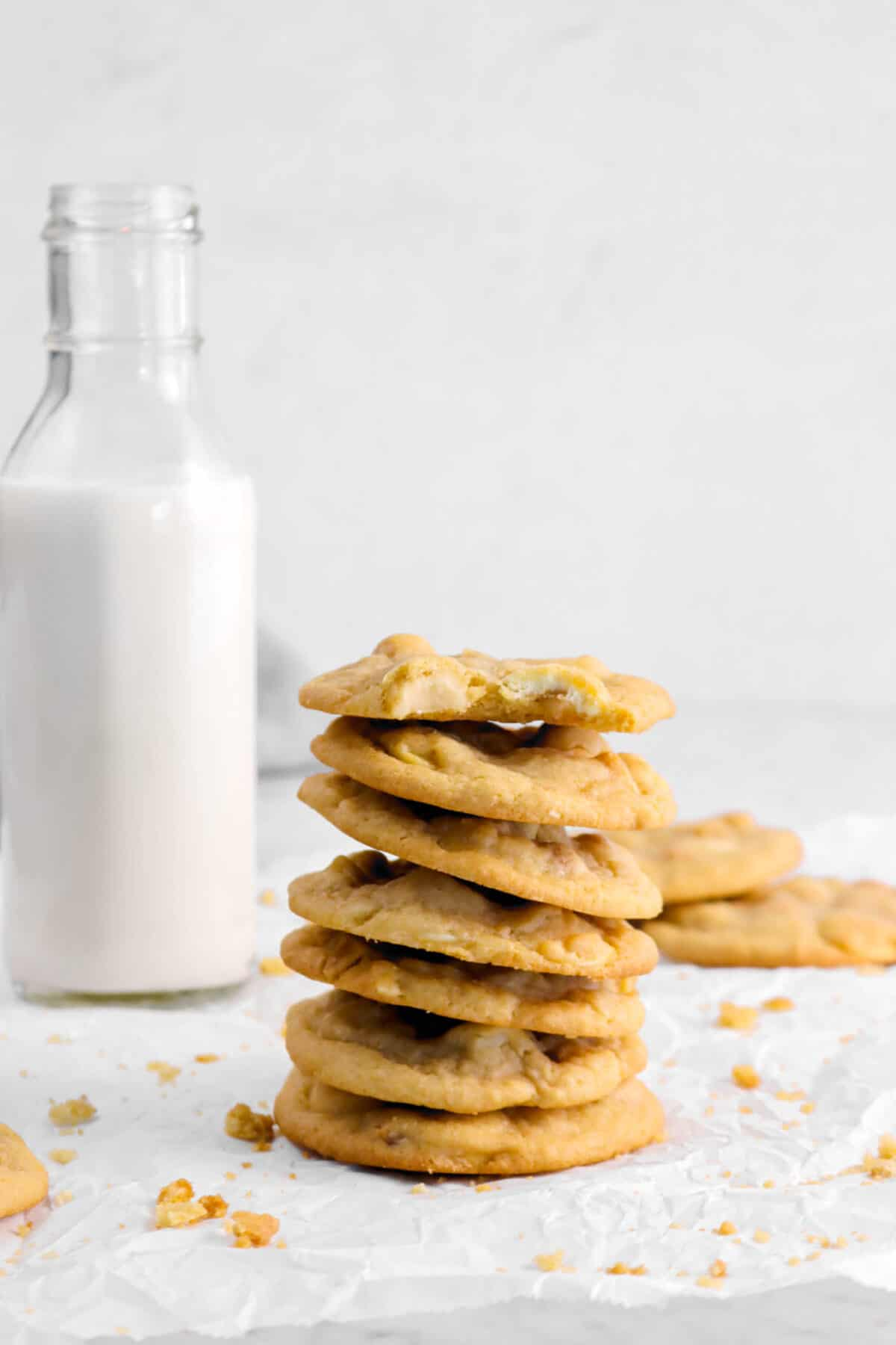 seven stacked cookies with a bite taken out of one with glass of milk behind
