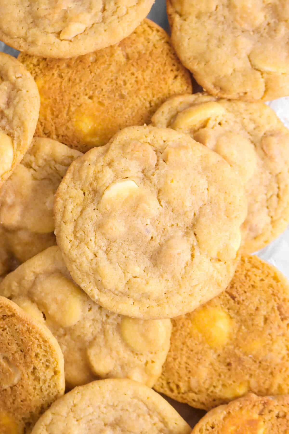 ten white chocolate macadamia nut cookies on parchment with some upside down