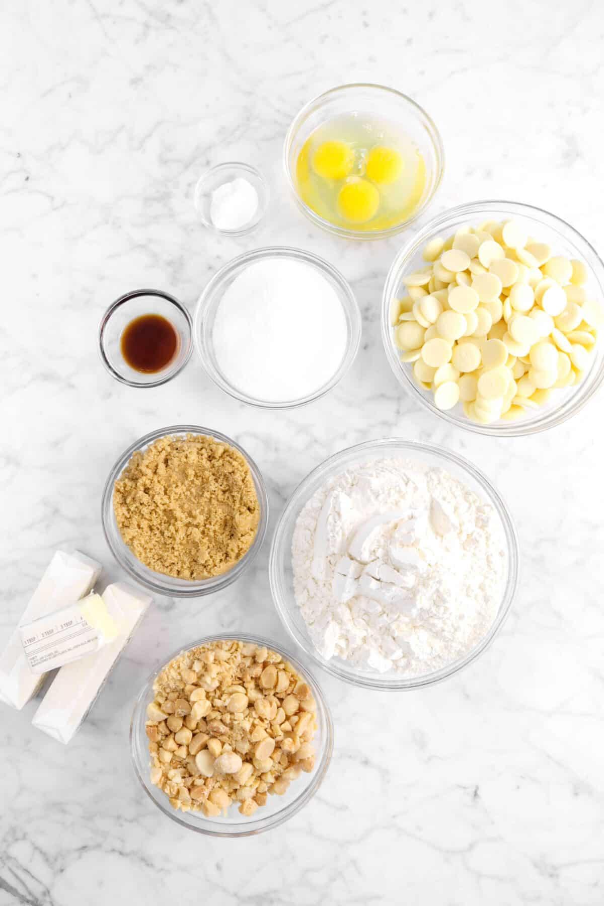 baking soda, eggs, white chocolate, sugar, vanilla, brown sugar, flour, chopped macadamia nuts, and butter on marble counter