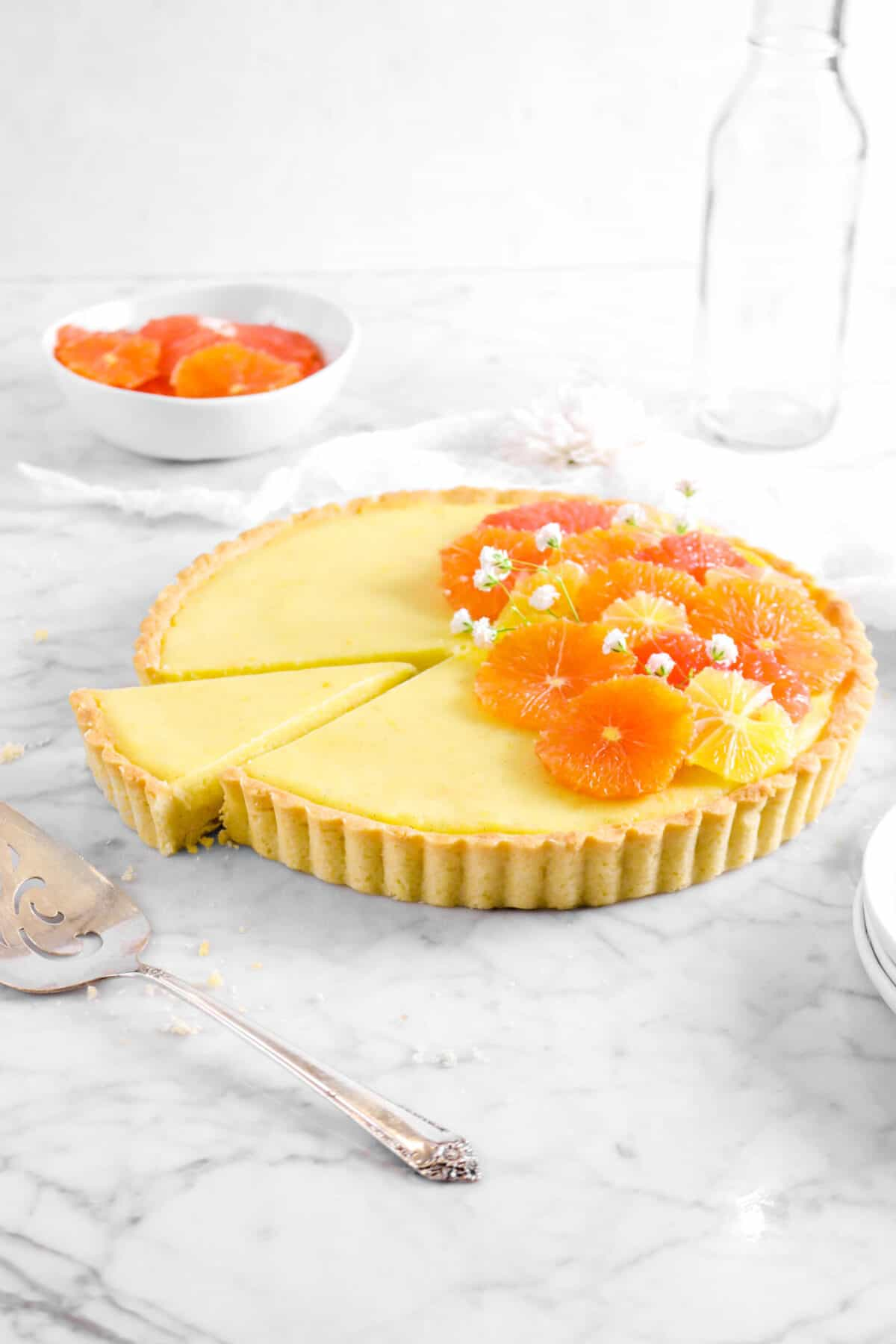 citrus tart with slice taken out of it on marble counter with sliced citrus, cake knife, and glass