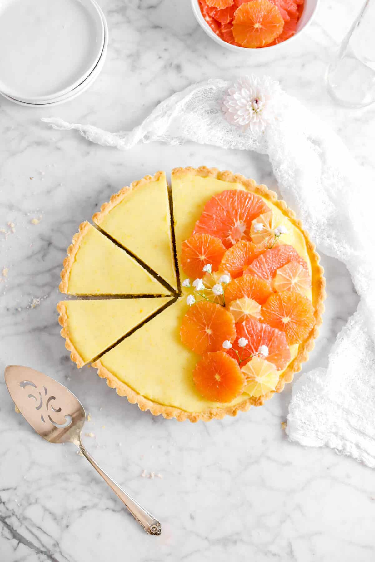 overhead shot of citrus tart with cake knife, white napkin, flowers, and white paltes