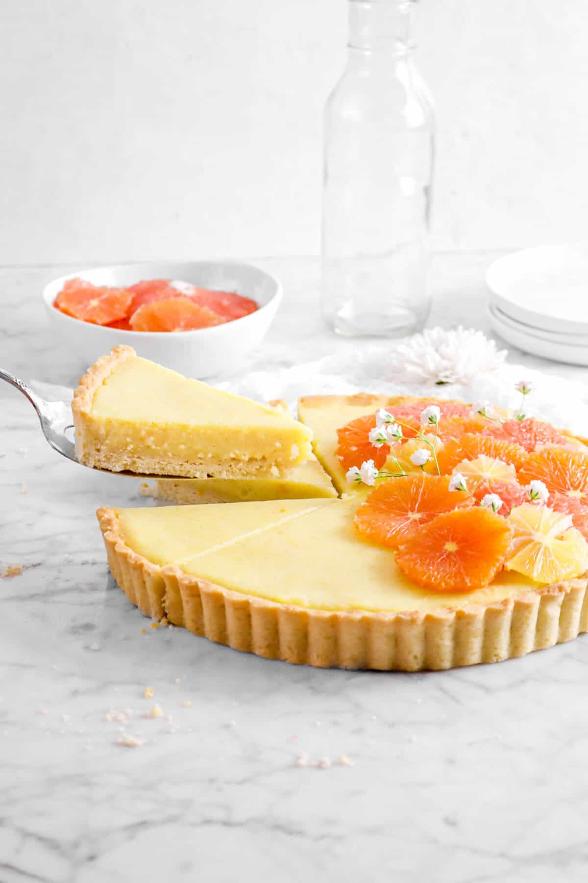 slice of citrus tart being held above the rest of the tart with bowl of citrus, glass, and stacked plates behind