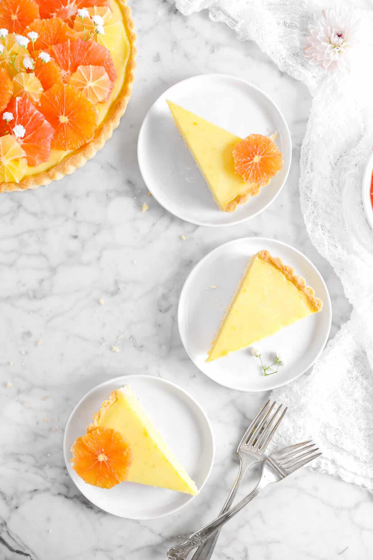 three slices of citrus tart on white plates with two forks and napkin
