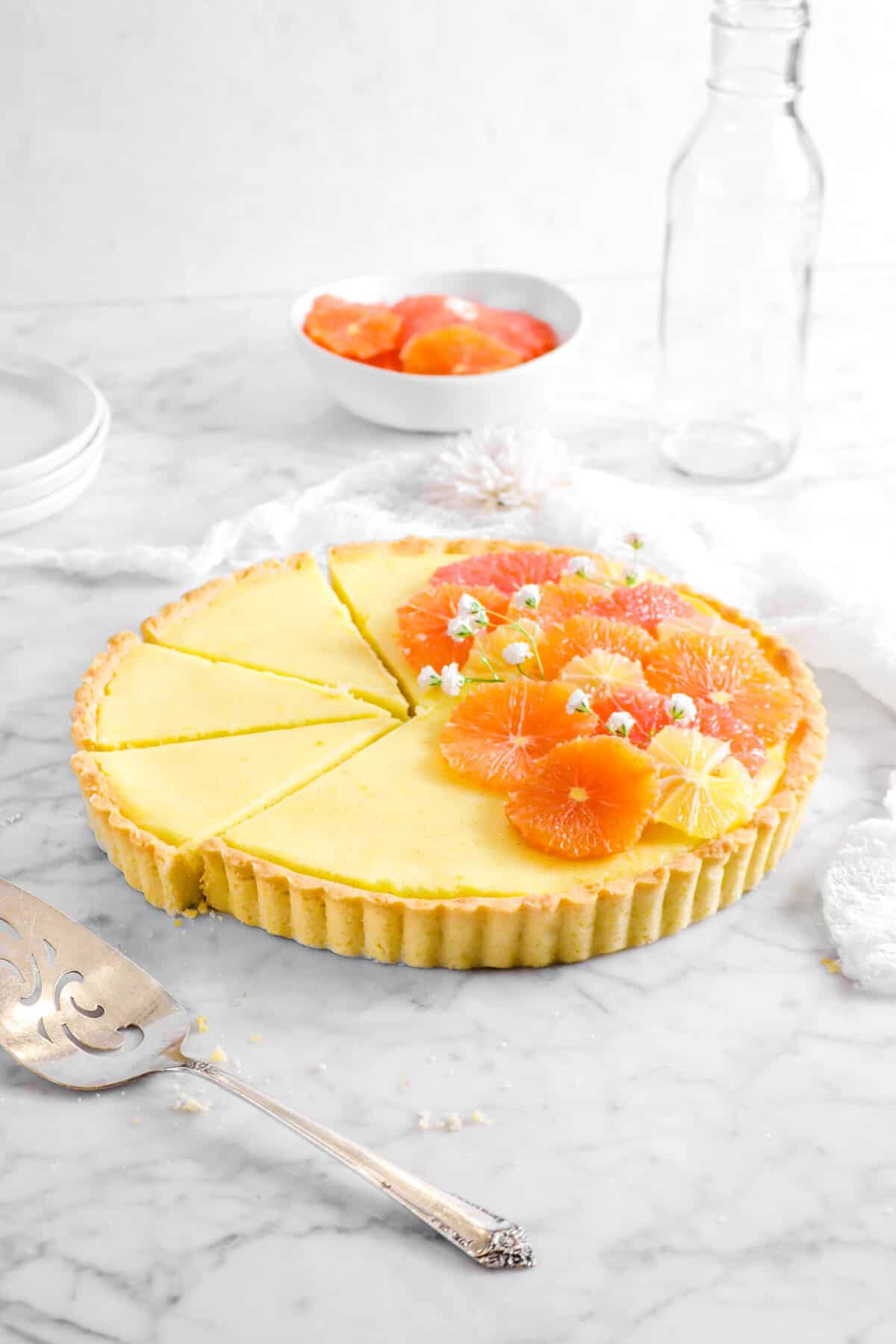 citrus tart with three slices laying next to it, a cake knife, white napkin, glass, and bowl of citrus slices