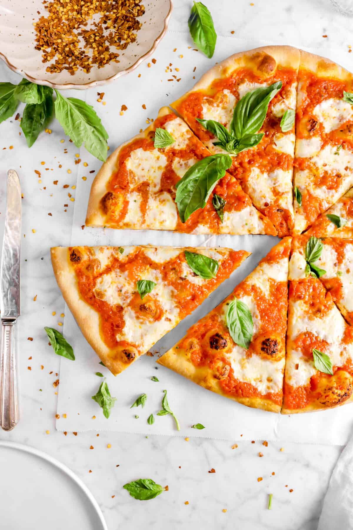 pizza slice pulled away from pizza on parchment with red pepper flakes, basil leaves, a knife, and plate
