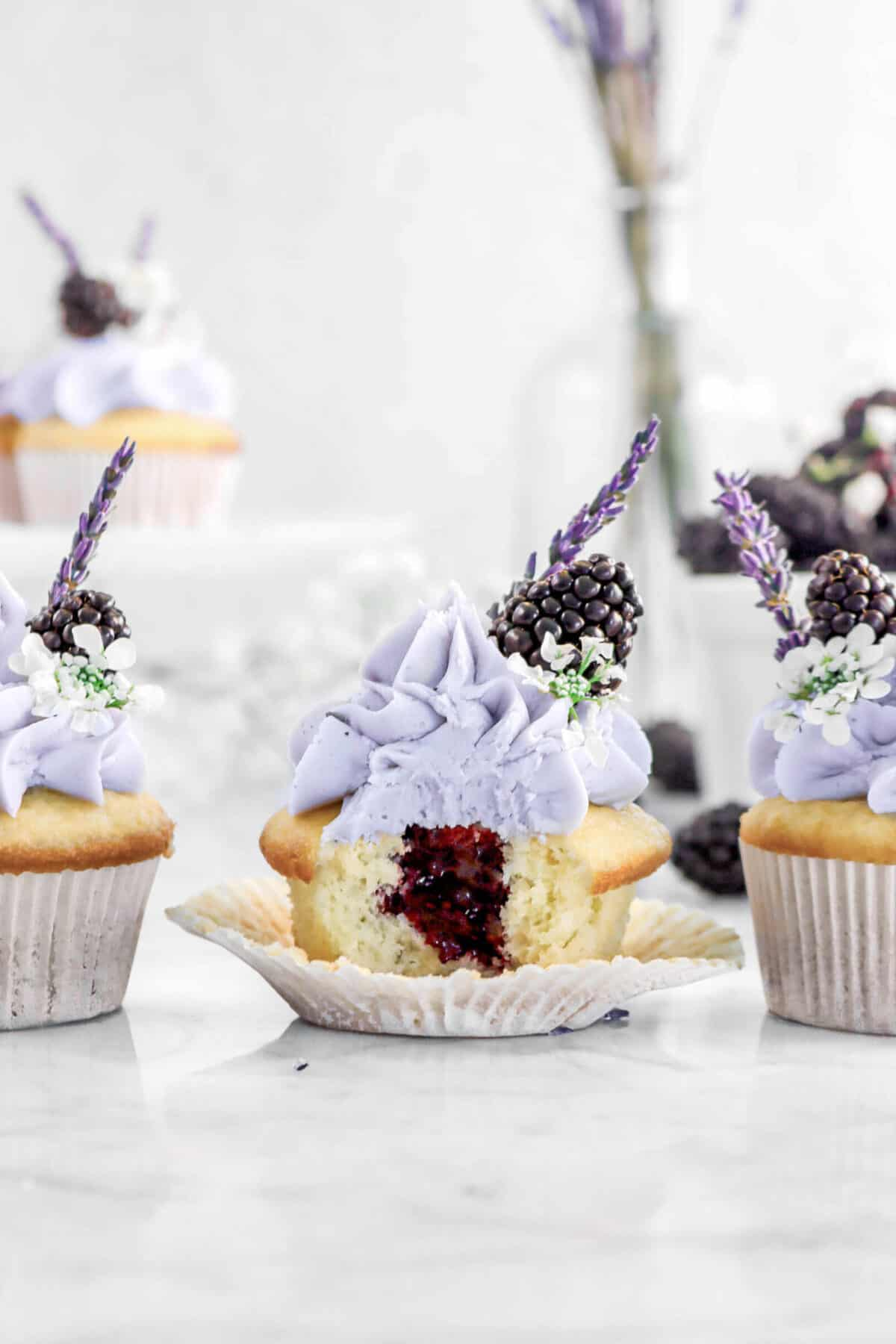 three cupcakes in a line with a bite taken out of one with flowers, blackberries, and more cupcakes behind