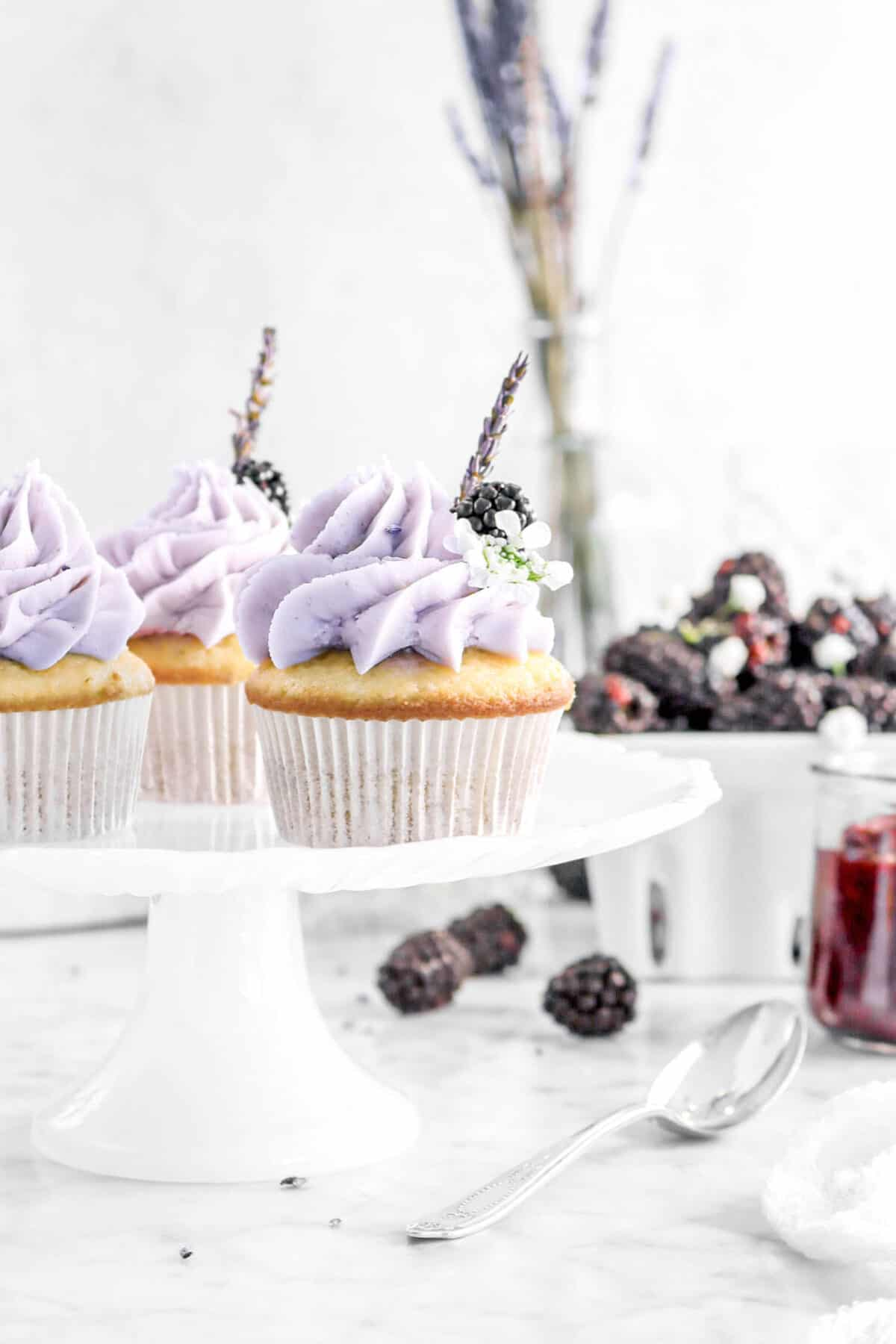 three cupcakes on white cake plate with container o blackberries, fresh flowers, and jar of jam with a spoon