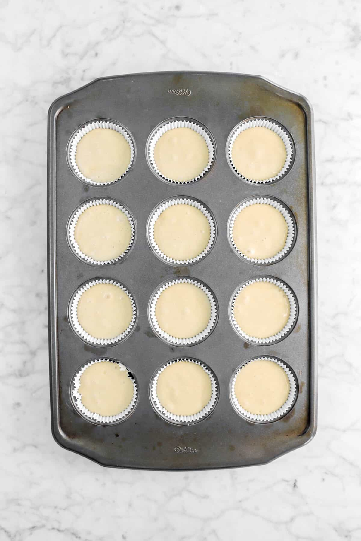 twelve unbaked cupcakes in a pan
