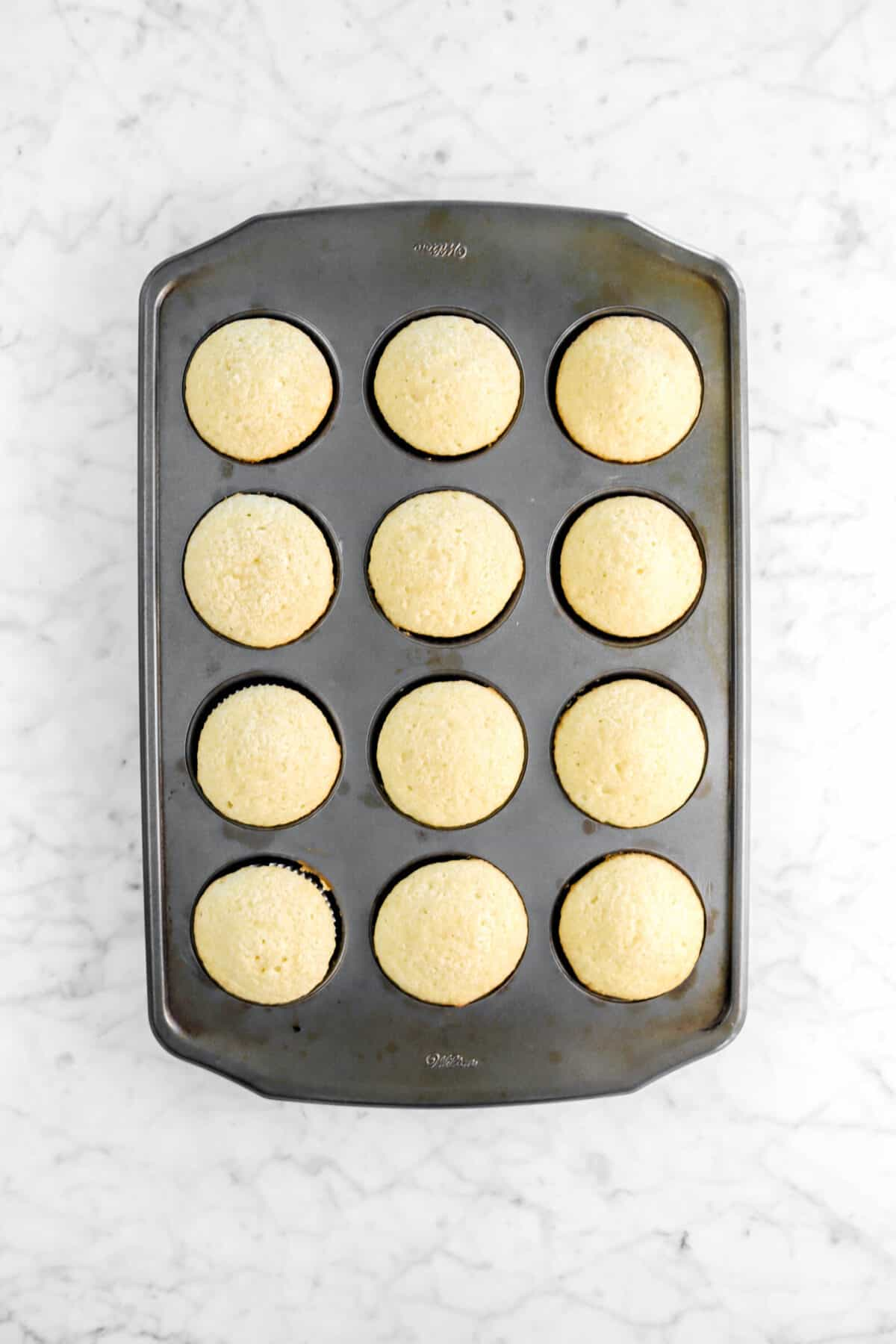 twelve baked cupcakes in a pan