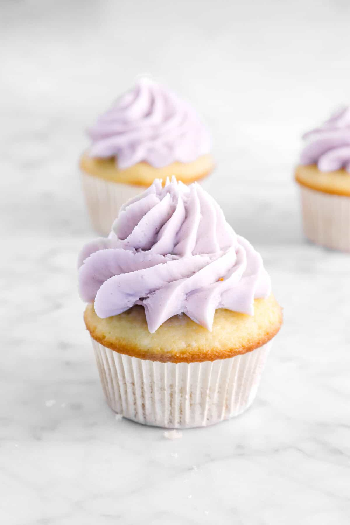 three cupcakes with lavender frosting on top