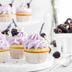cupcakes on marble serving board with blackberries, lavender, white flowers, and a spoon