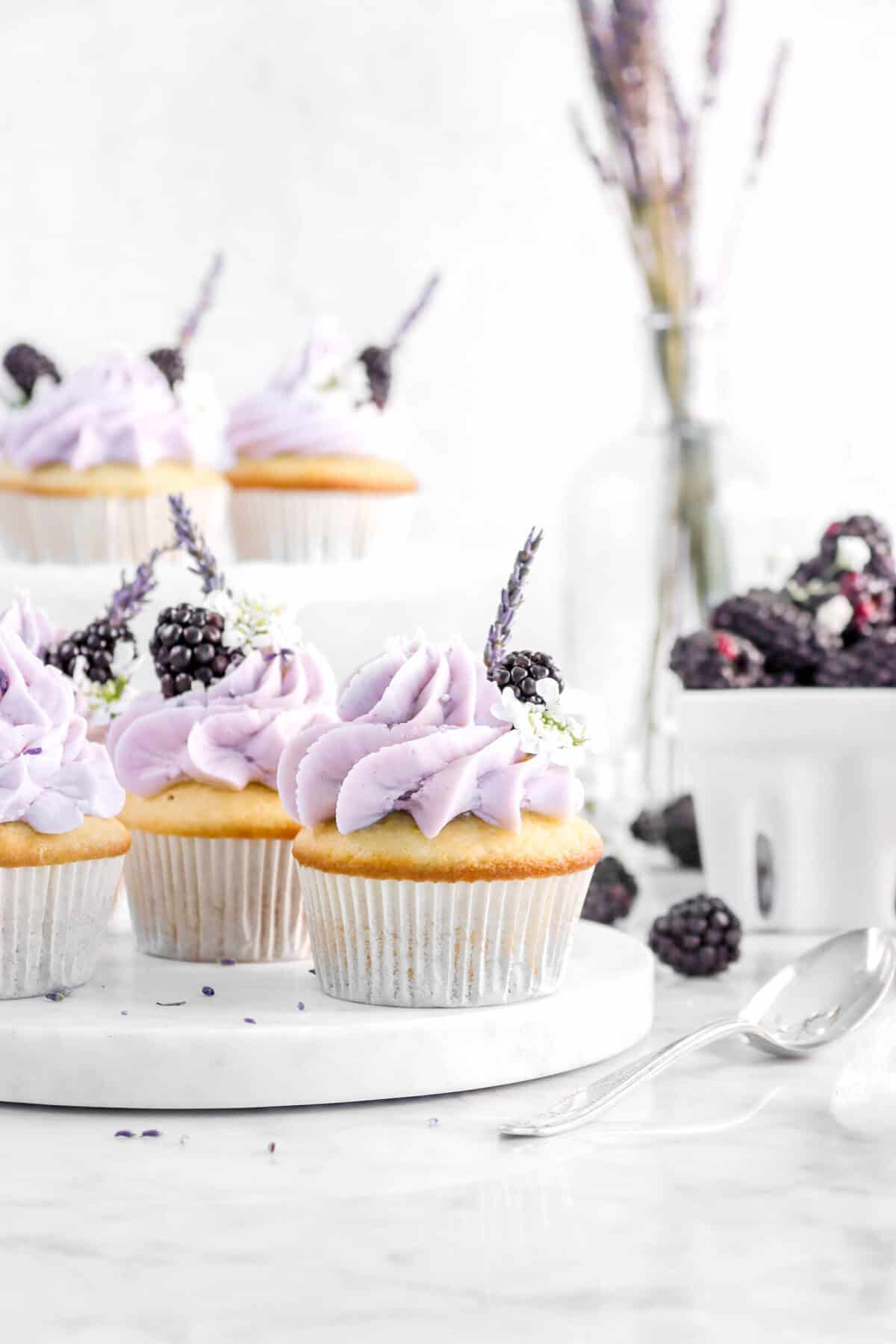 three cupcakes on marble server with more cupcakes behind, jar of lavender, container of blackberries, and a spoon