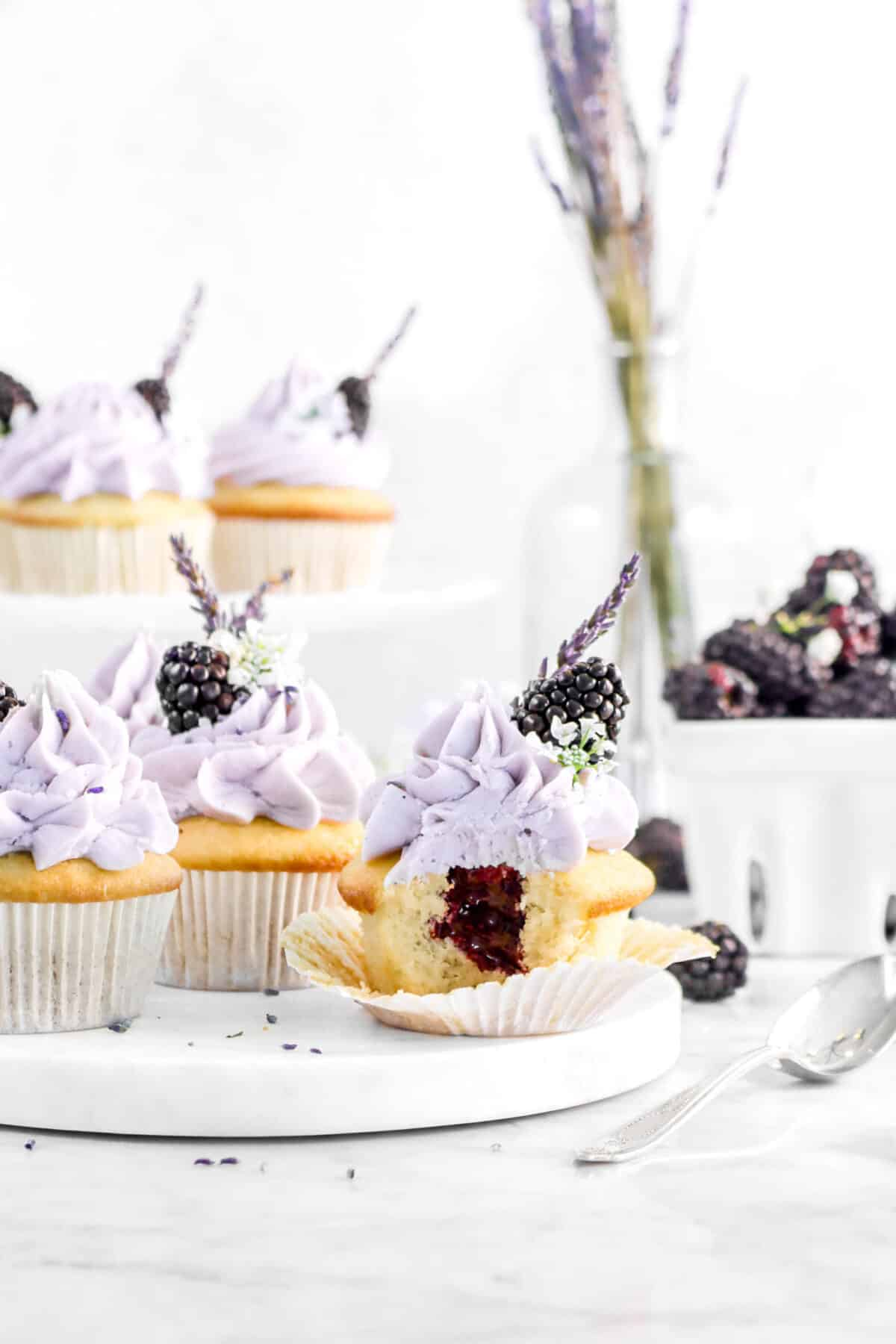 blackberry lavender cupcakes with a bite taken out of one with jam in the middle, blackberries around, and lavender