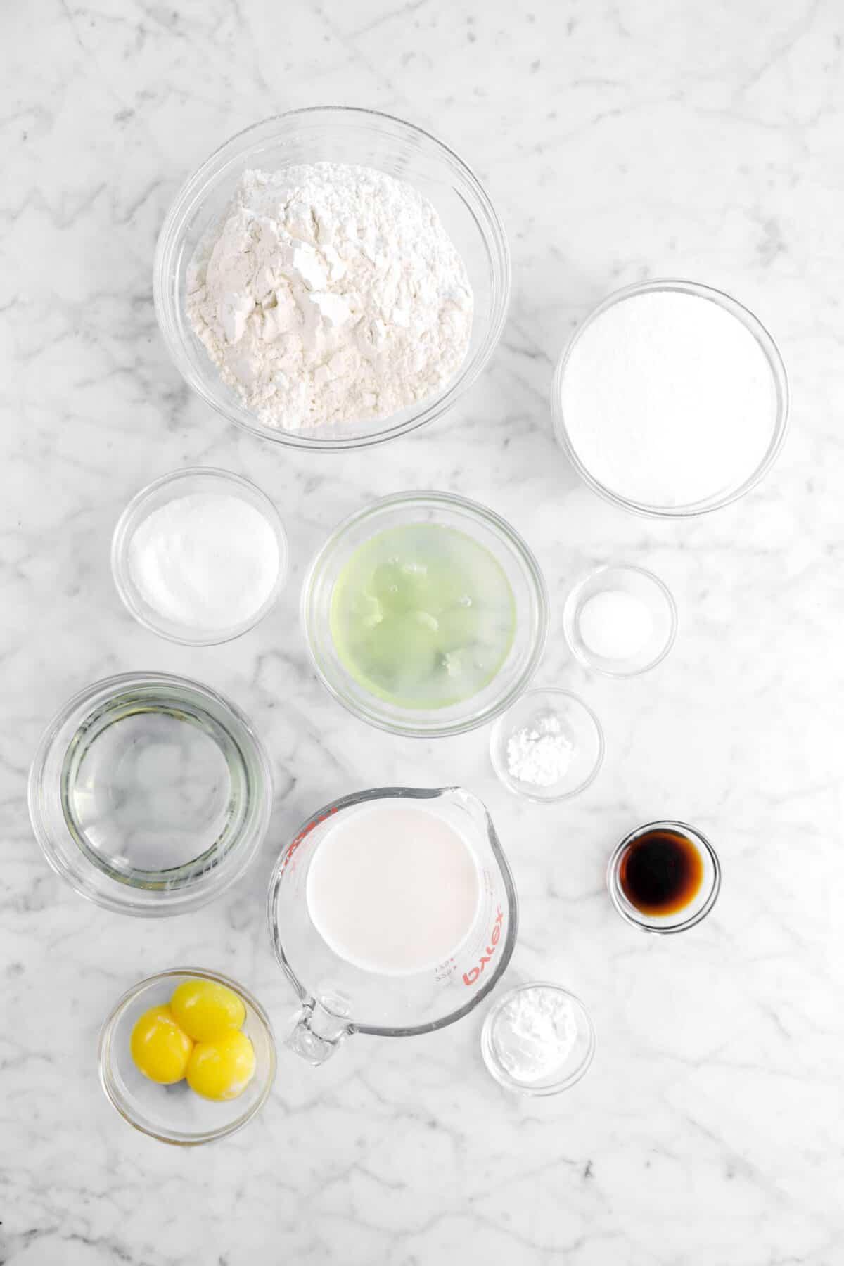 flour, sugar, egg whites, salt, cream of tar tar, vegetable oil, milk, vanilla, baking powder, and egg yolks in glass bowls