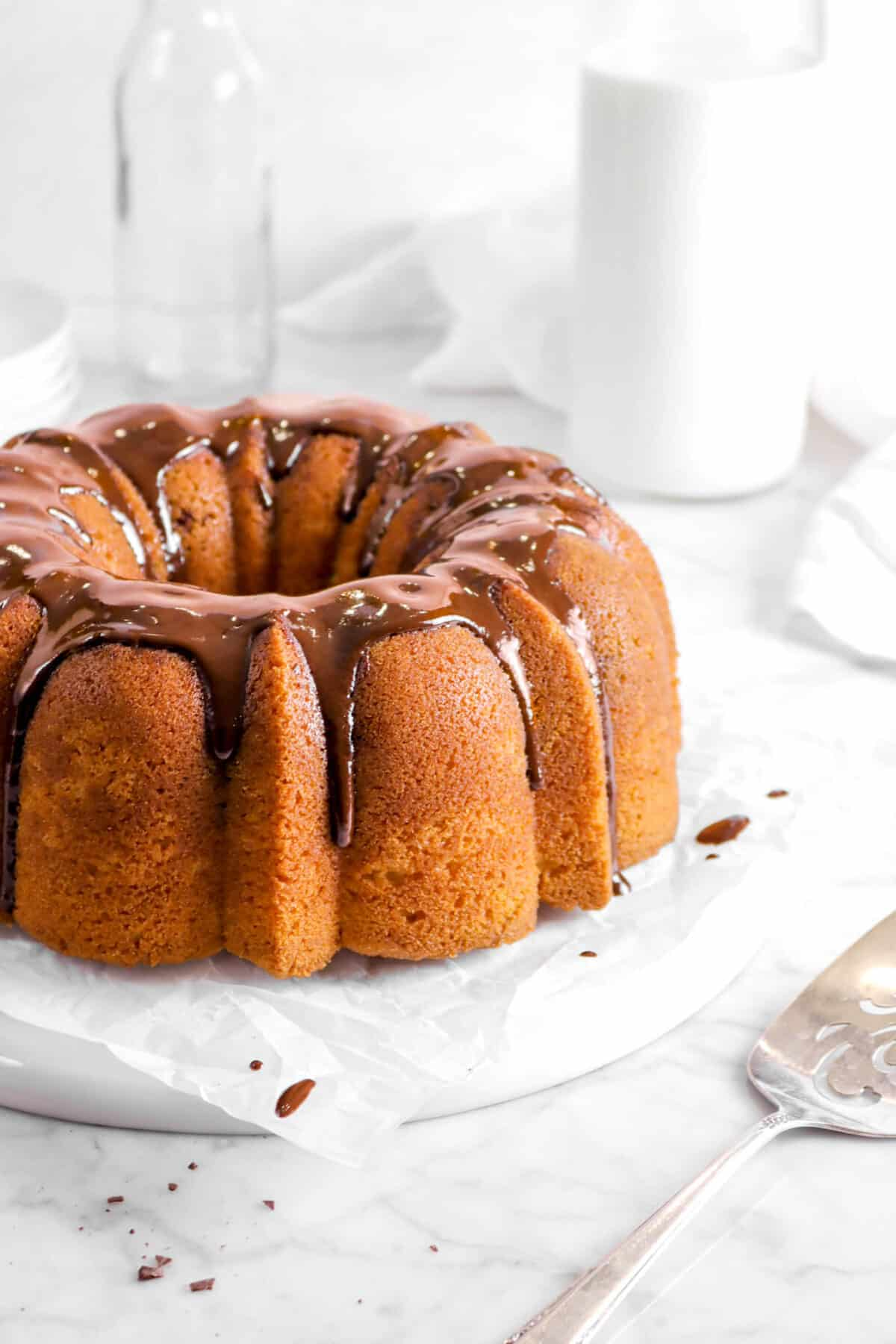 close up of bundt cake on parchment with glass of milk, napkin and cake knife