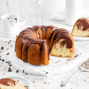 chocolate marble pound cake on parchment with a slice in front and a slice behind, glass of milk, two empty glasses, a creamer, and cake knife