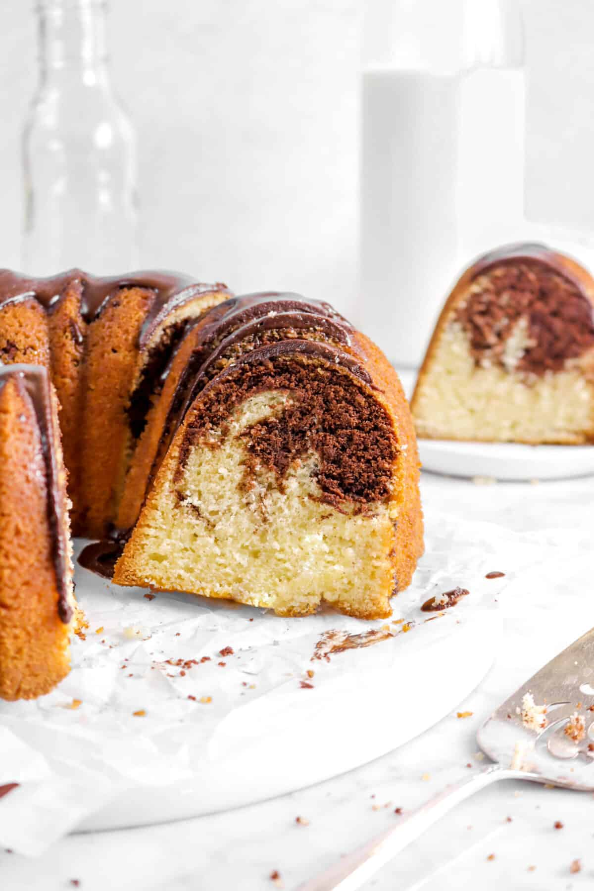 close up of chocolate marble pound cake with slice behind and glass of milk