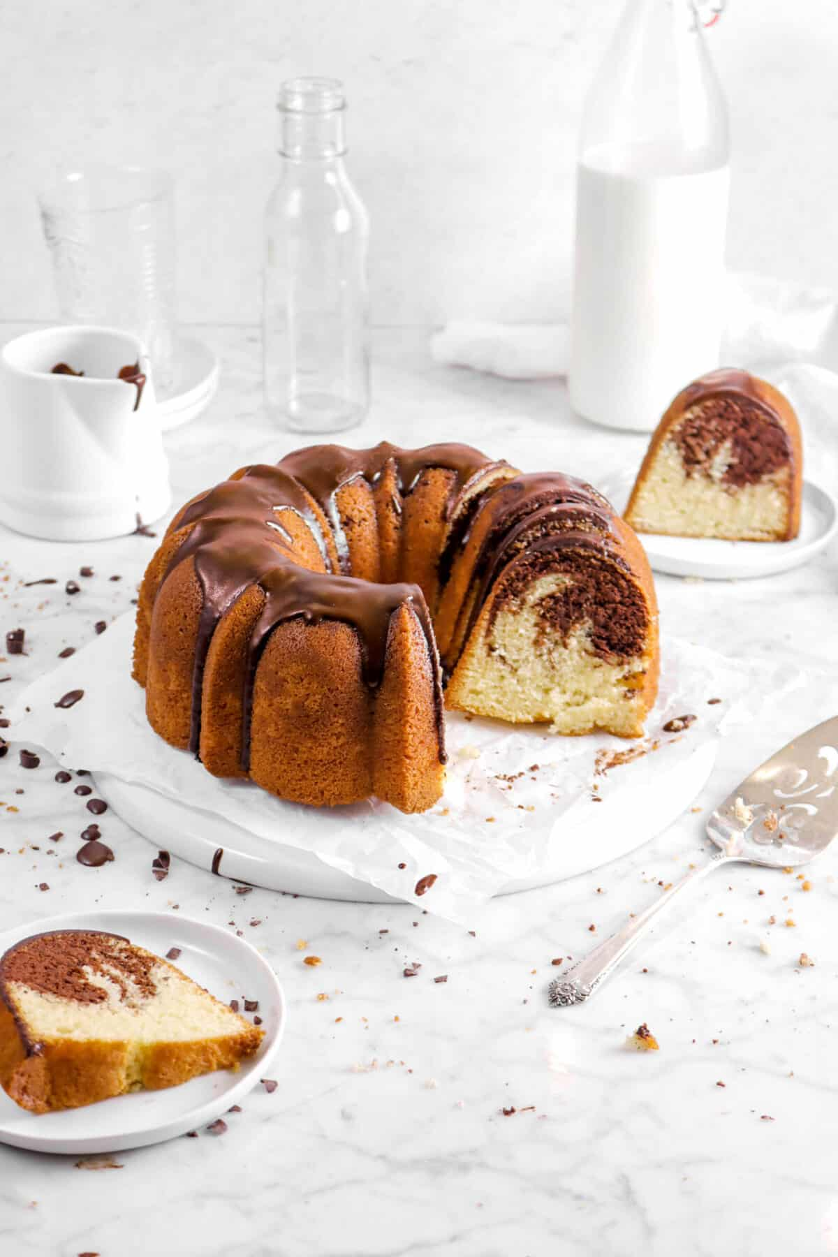 chocolate marble pound cake on upside down plate on parchment with a slice in front on a white plate and a slice behind on a white plate with a cake knife, glass of milk, a napkin, two empty glasses, and creamer glass