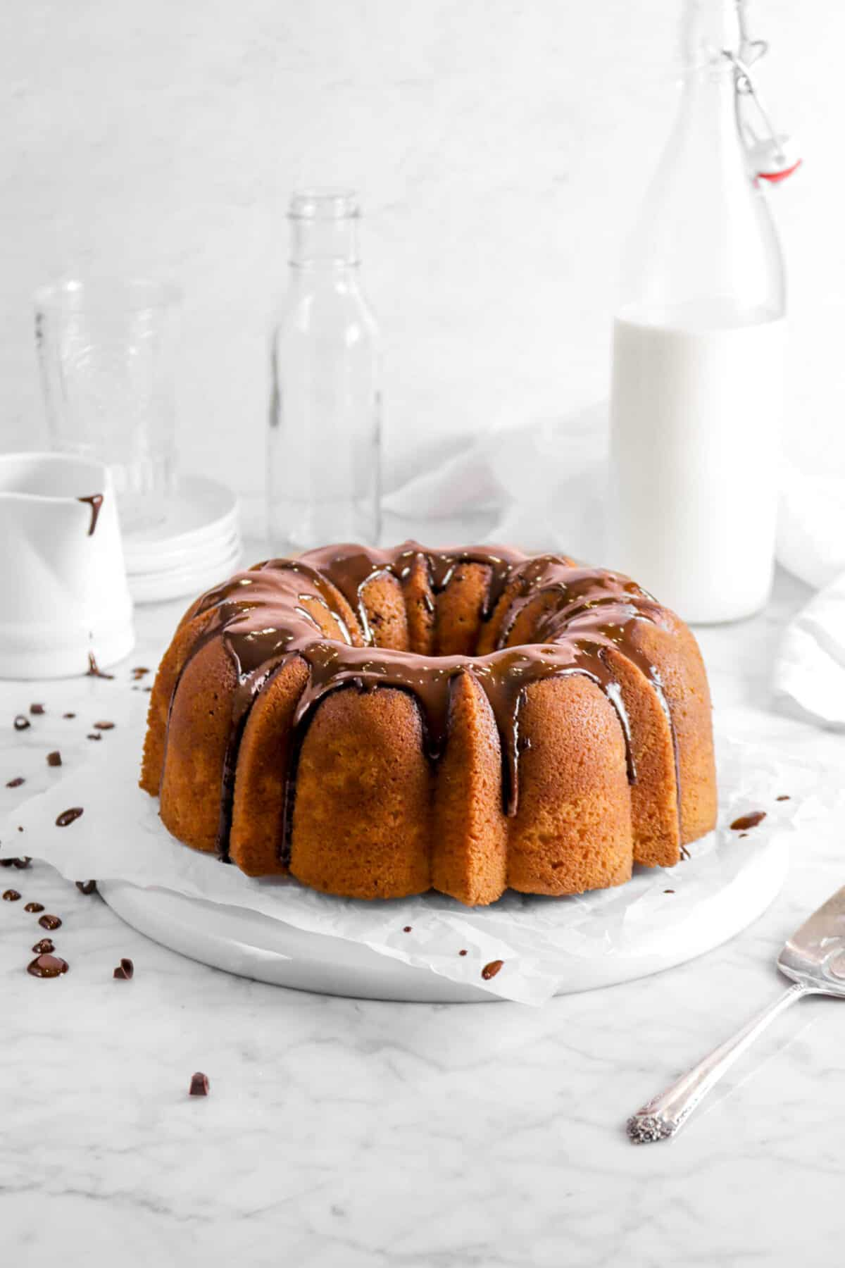 chocolate marble pound cake with chocolate ganache dripping on parchment paper with glass of milk, napkin, and two empty glasses