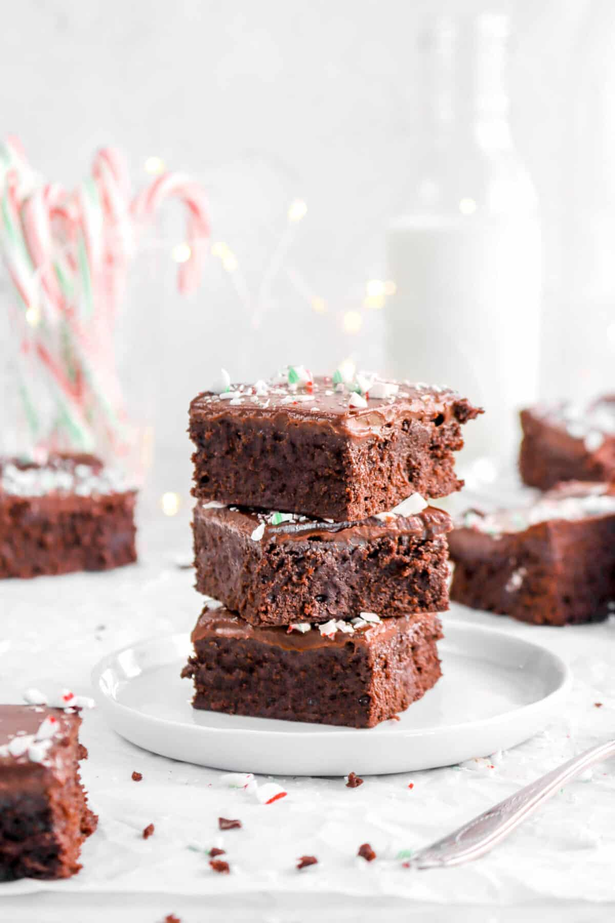 three stacked brownies on white plate with candy canes, glass of milk, fairy lights, and more brownies behind
