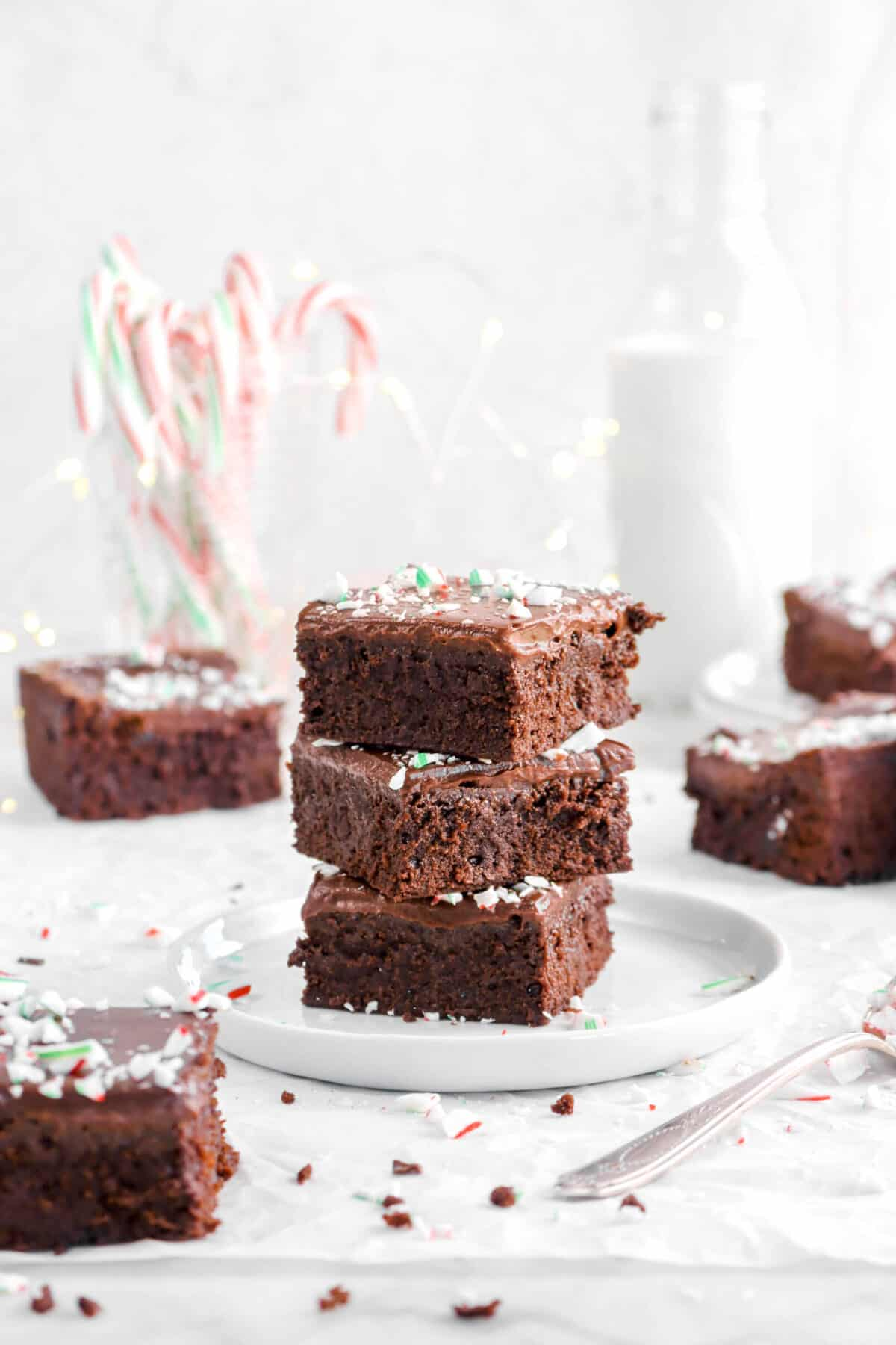 three stacked browies on white plate with more brownies around, candy canes, and milk glass behind
