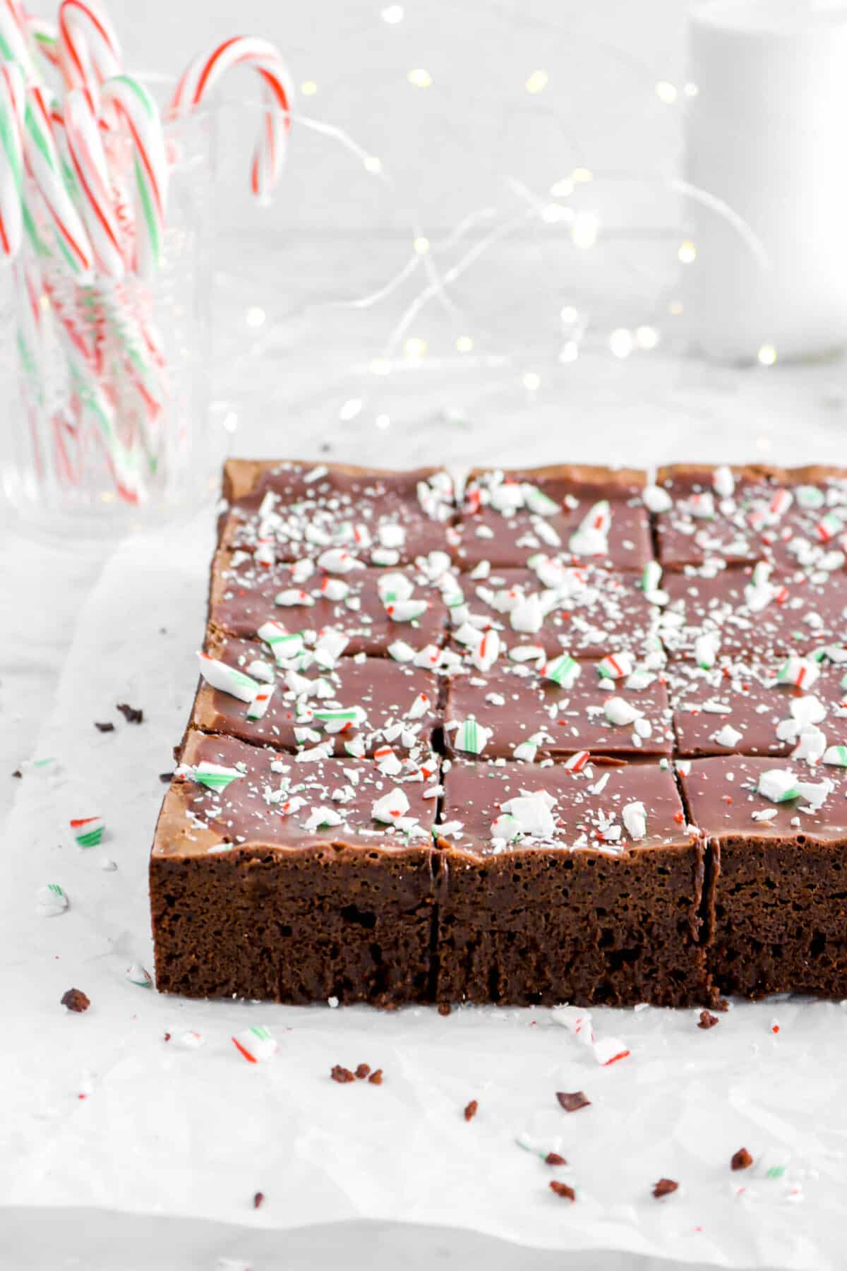 peppermint brownies on pachment with glass of candy canes and fairy lights