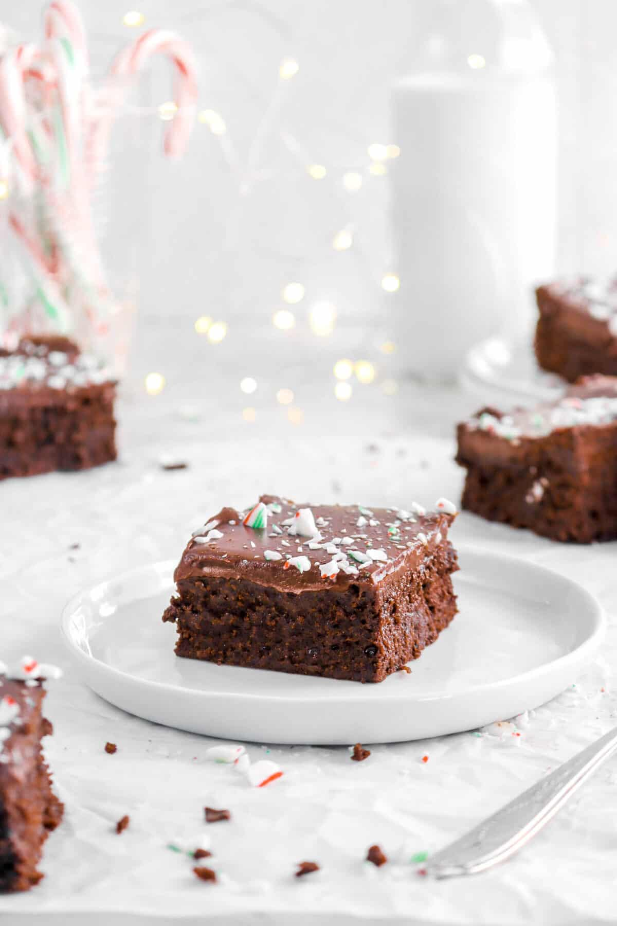 peppermint brownie on white plate with more brownies behind, fairy lights, and glass of milk