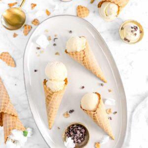 three cones of irish cream ice cream on server with cones around, chocolate curls, gold spoon, and gold bowl of ice cream