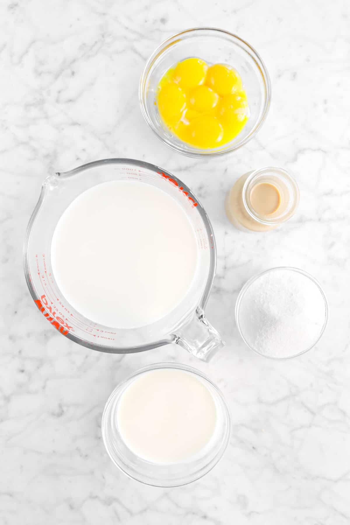 egg yolks, irish cream, sugar, heavy cream, and milk in bowls on marble counter