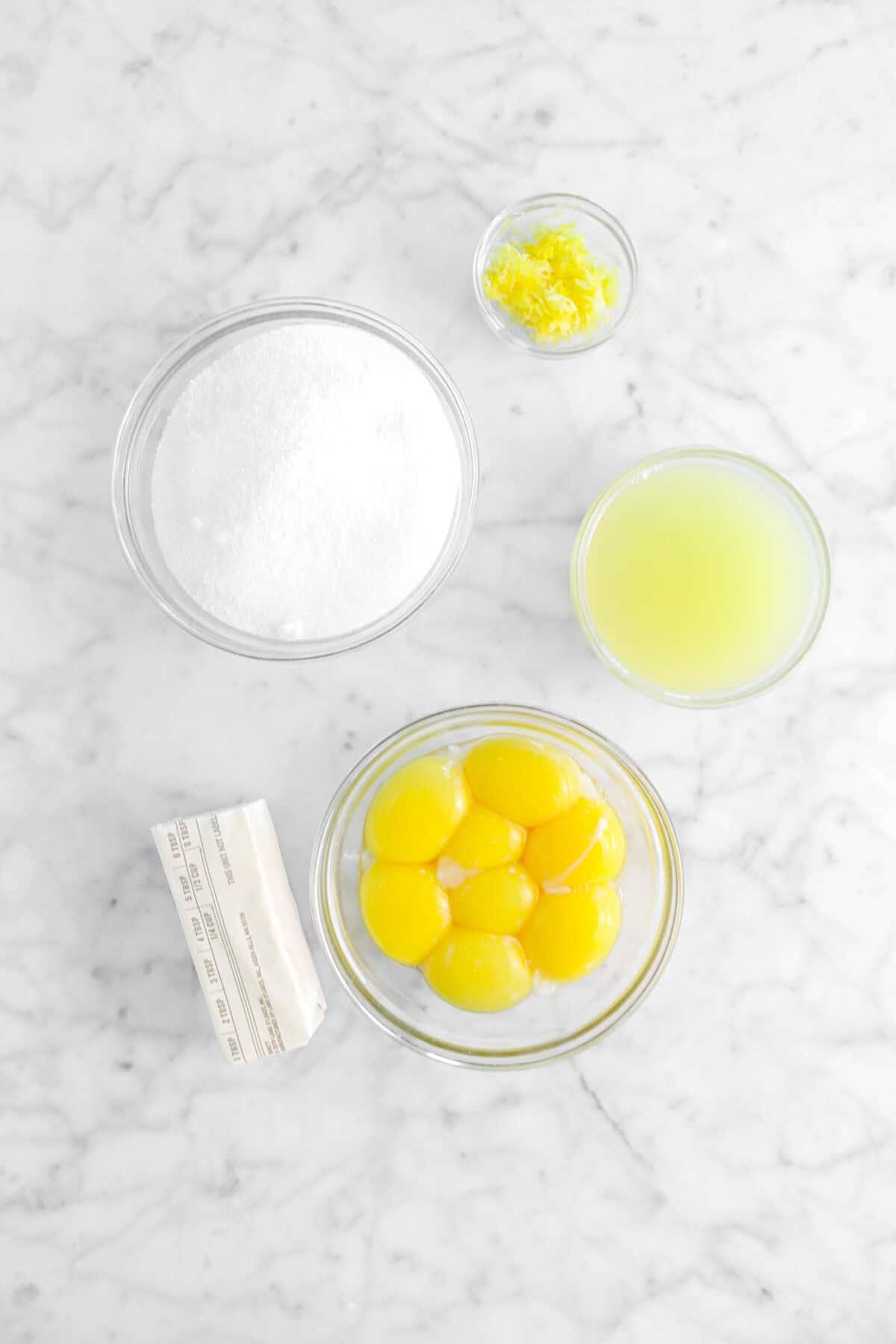 lemon zest, sugar, lemon juice, egg yolks, butter on marble counter