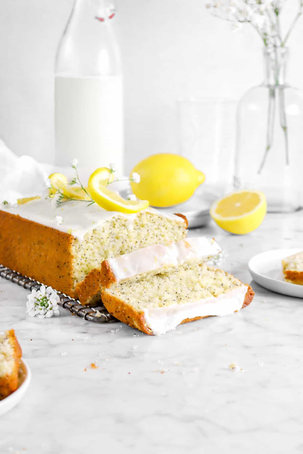 two slices of lemon bread laying in front of loaf with flowers, lemon twists, and a jug of milk