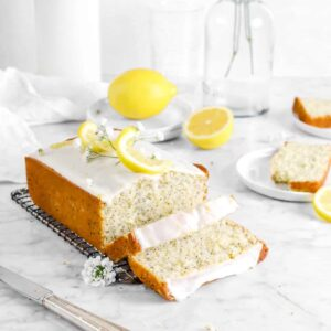 lemon poppy seed bread on wire cooling tack with two slices laying in front, two slices behind, lemons behind, a vase, white napkin, and jug of milk