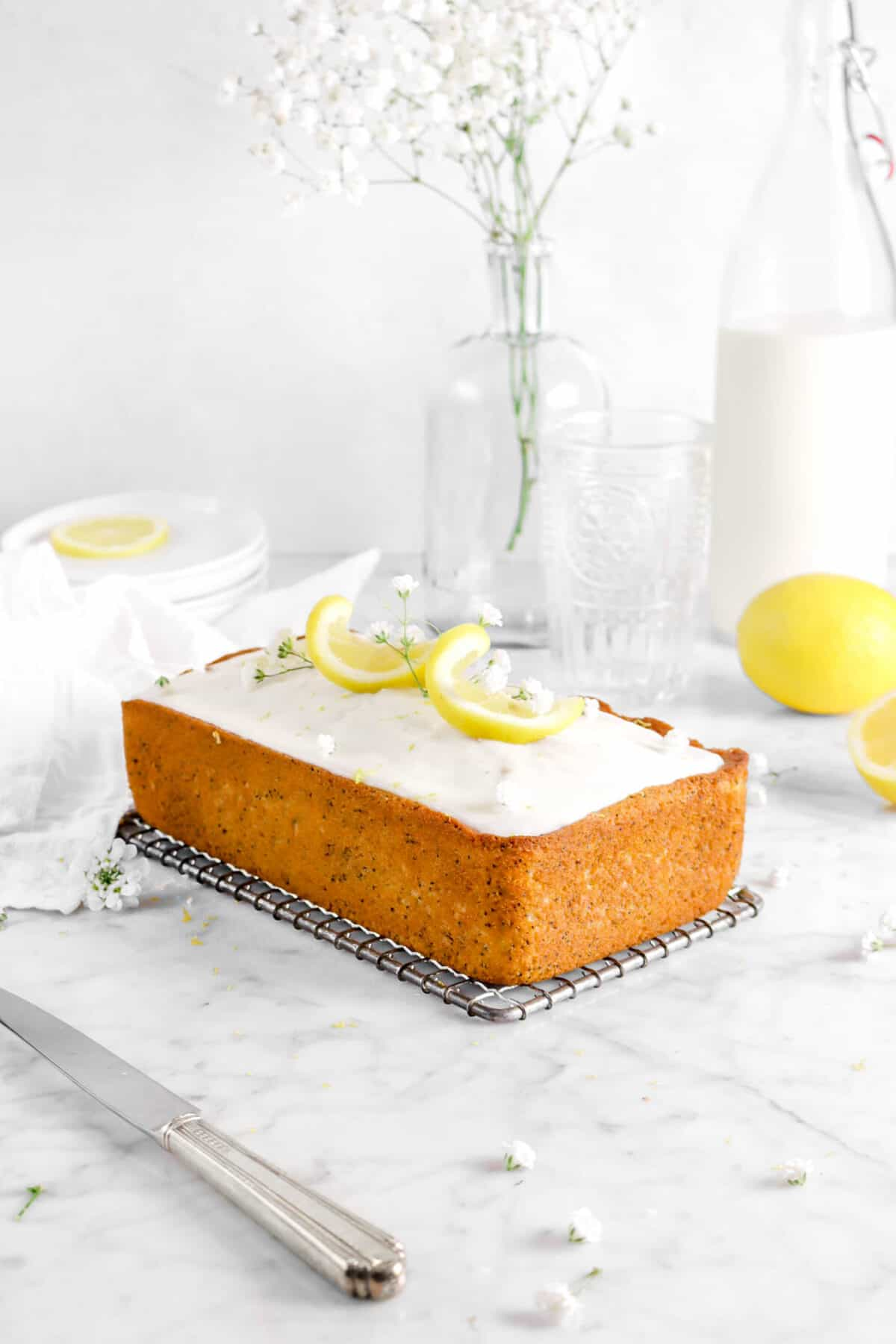 lemon poppy seed bread on wire cooling rack with lemon twists, flowers, a knife, jug of milk, a glass, plates, and vase behind