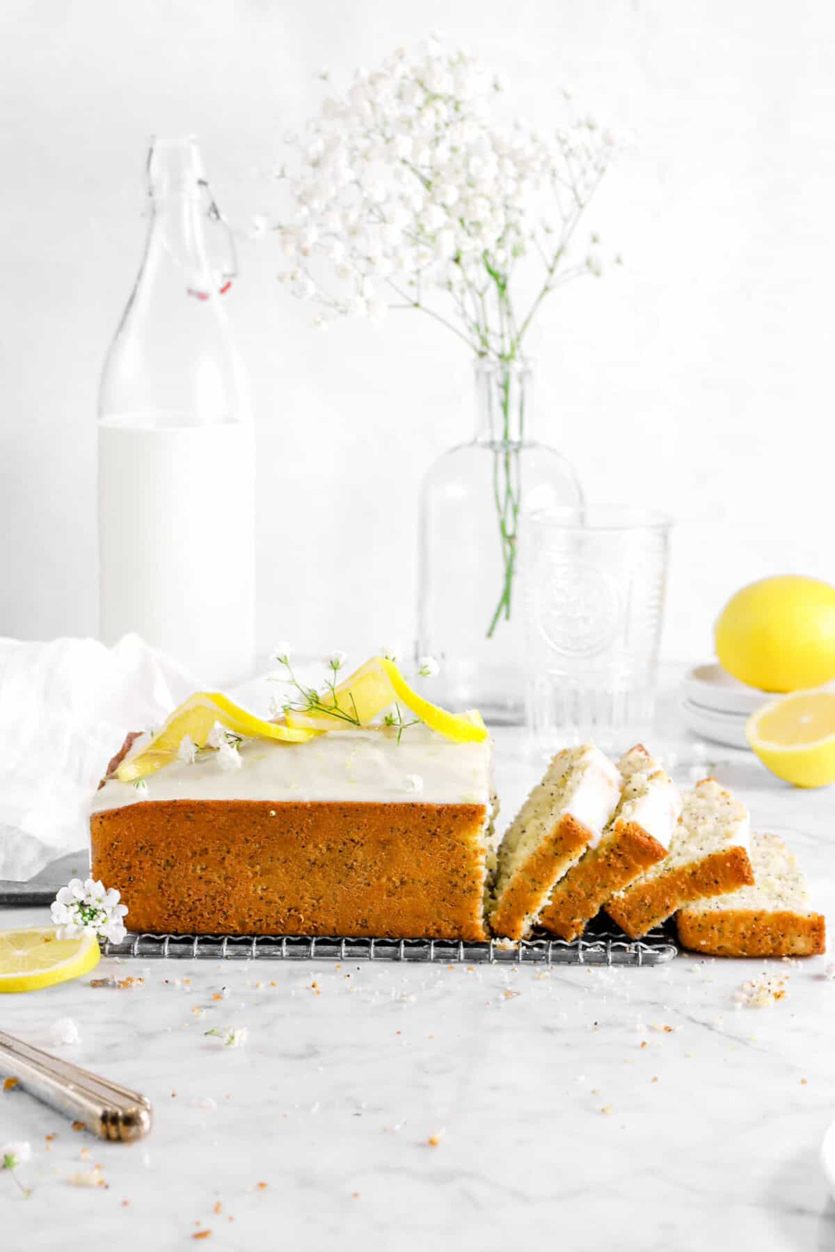 lemon poppy seed loaf side shot with four slices laying in front with jug of milk, a vase, glass, and lemons behind