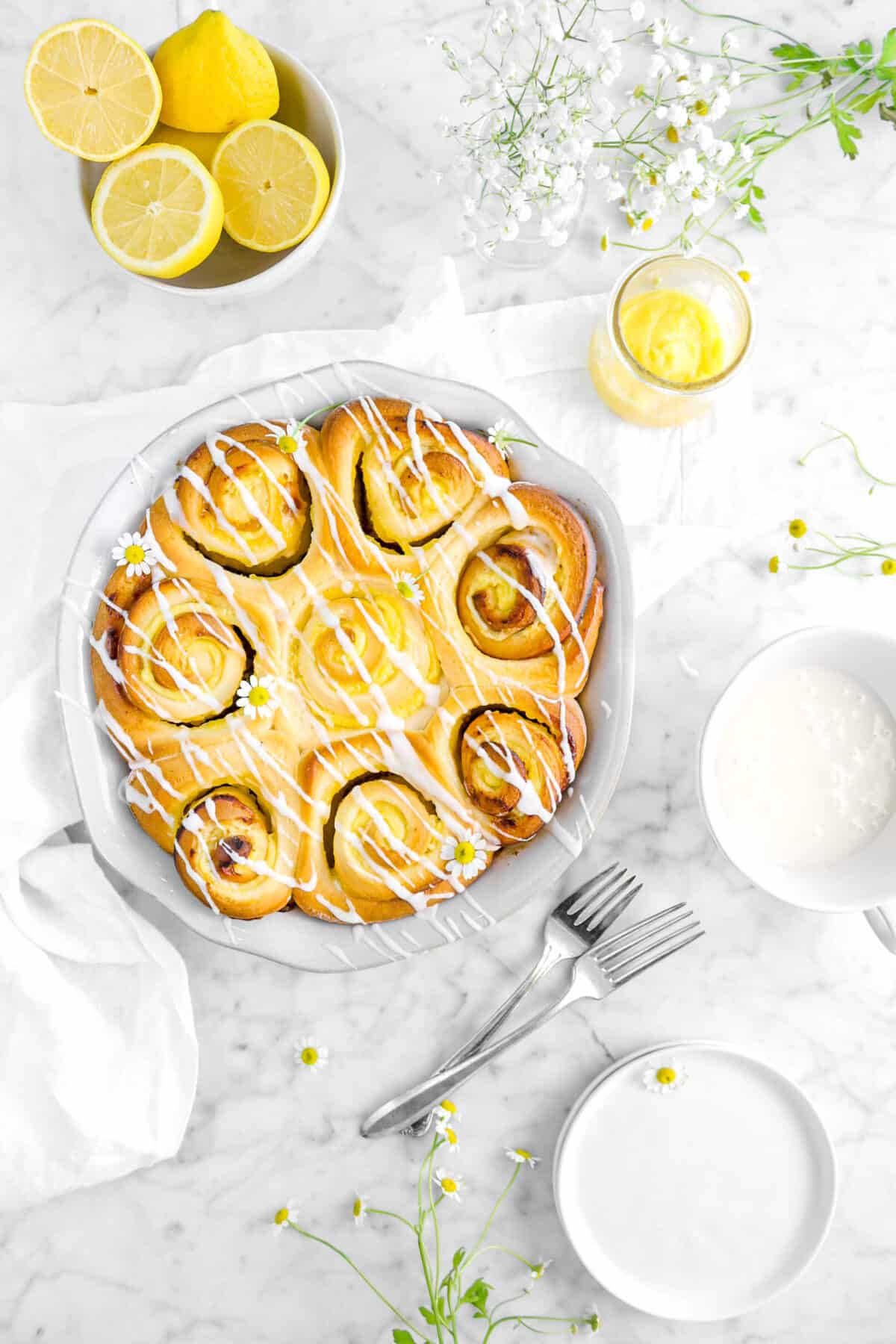 overhead shot of lemon rolls in pie pan with a napkin, forks, lemons, flowers, lemon curd, and plates