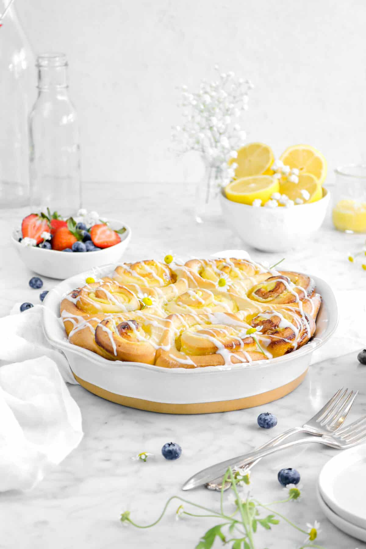 lemon sweet rolls in pie pan with berries, fruit, a bowl of lemons, flowers, and two glasses