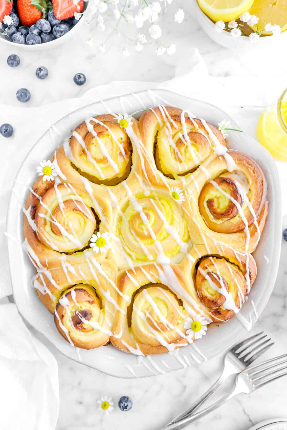 close up overhead shot of lemon rolls with blueberries, flowers, and forks