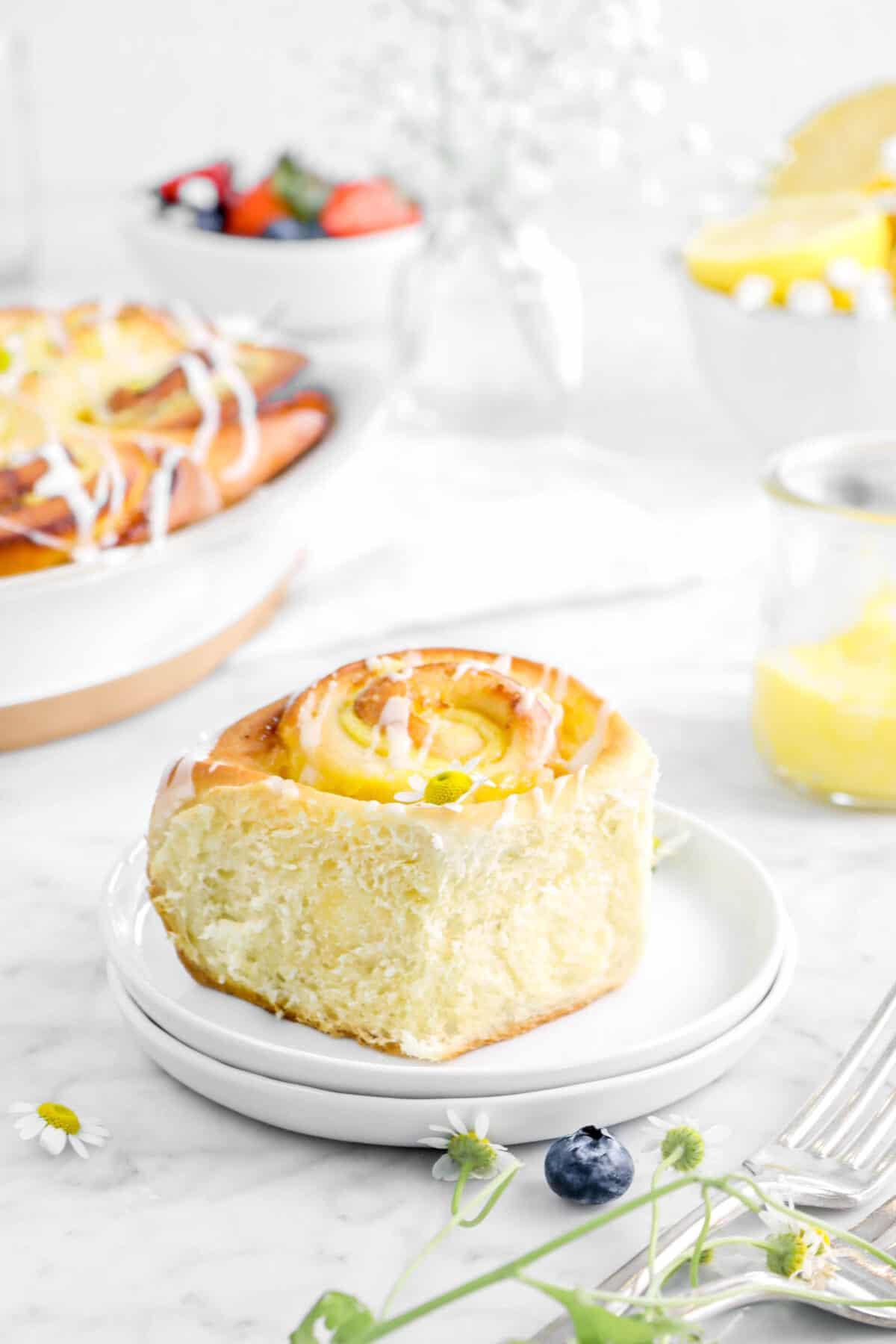 lemon sweer roll on two plates with flowers, lemon custard, berries, and rolls behind