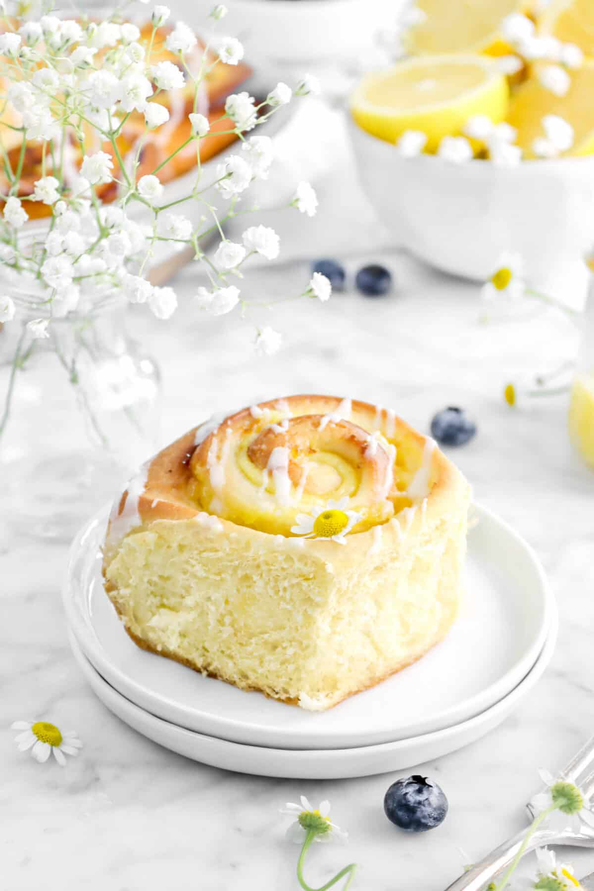 lemon roll on two plates with jar of white flowers, blueberries, and a bowl of lemons behind