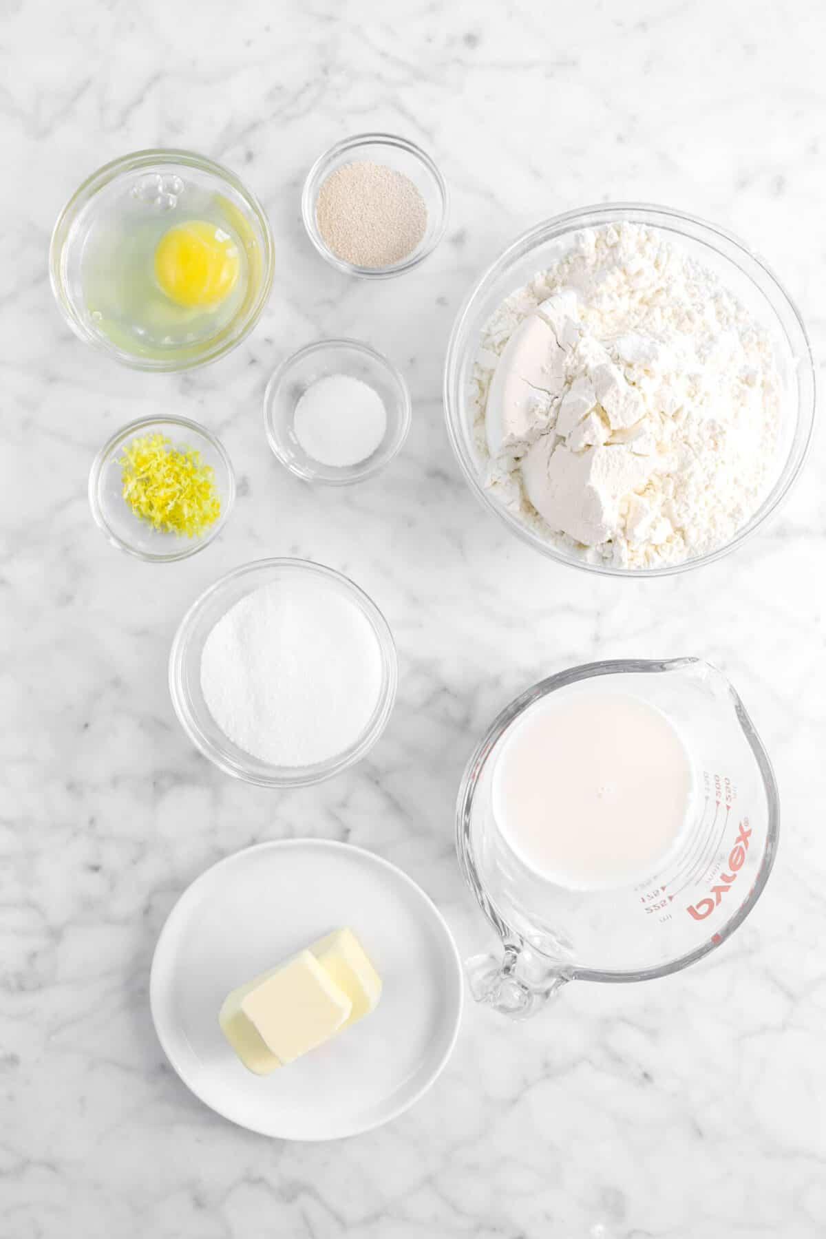 egg, yeast, flour, baking powder, lemon zest, sugar, milk, and butter on marble counter