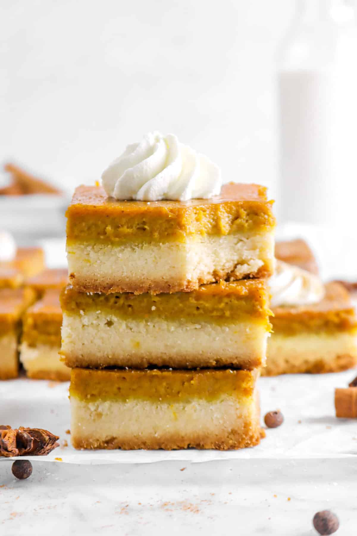 three stacked pumpkin bars with more bars behind, whole spices, and glass of milk