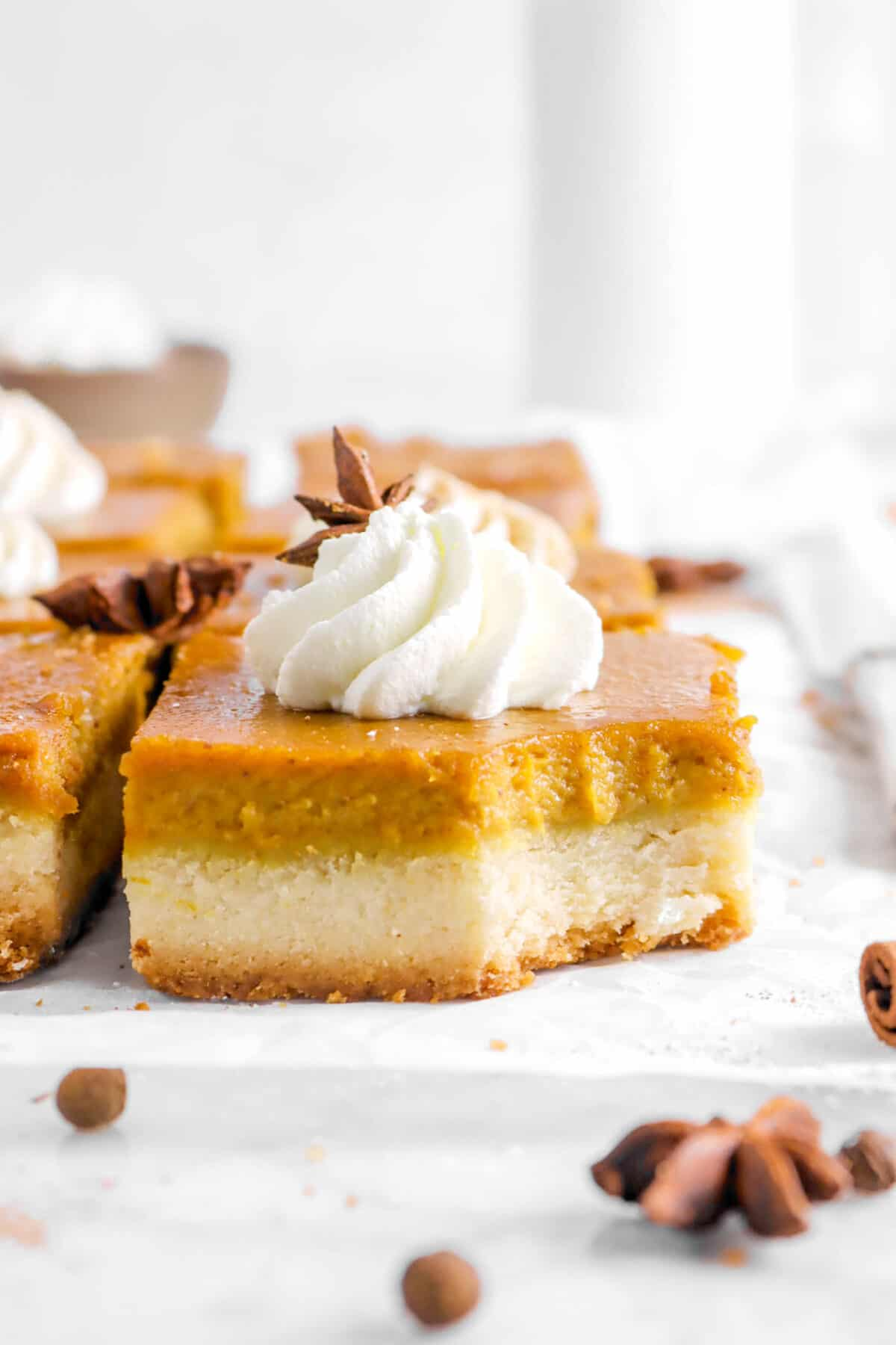 pumpkin bar with whipped cream, star anise, and a bite missing