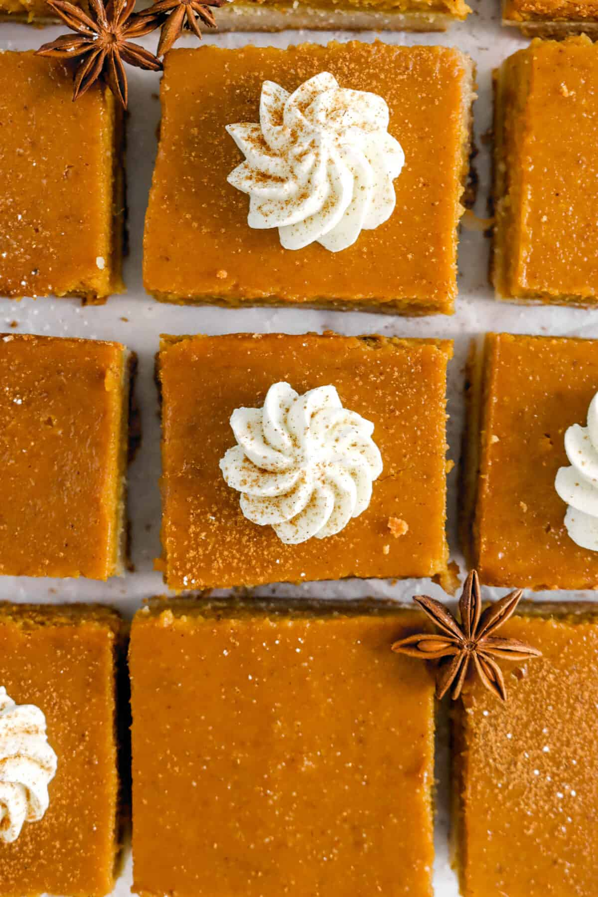 overhead shot of pumpkin pie bars, two having whipped cream, with two pods of star anise
