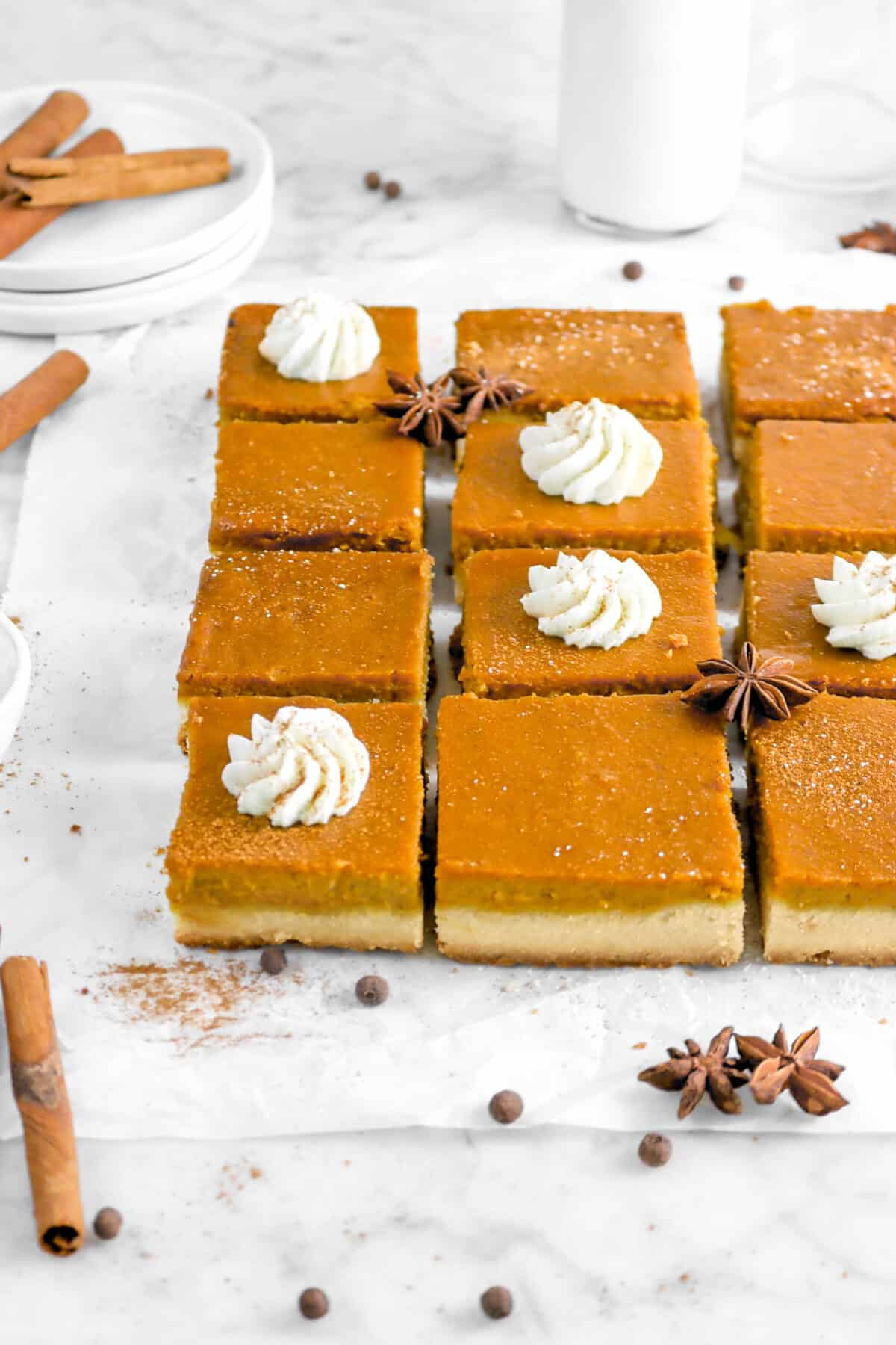 twelve pumpkin pie bars on parchment paper with whole spices, plates, and milk glass