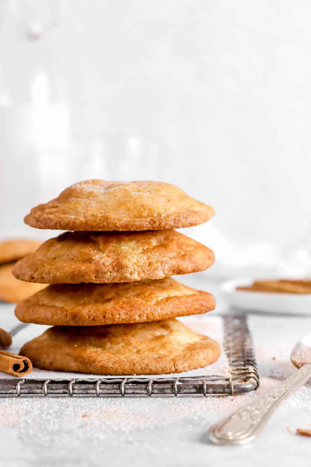 four stacked snickerdoodle cookies on wire cooling rack with spoon and glass of milk behind