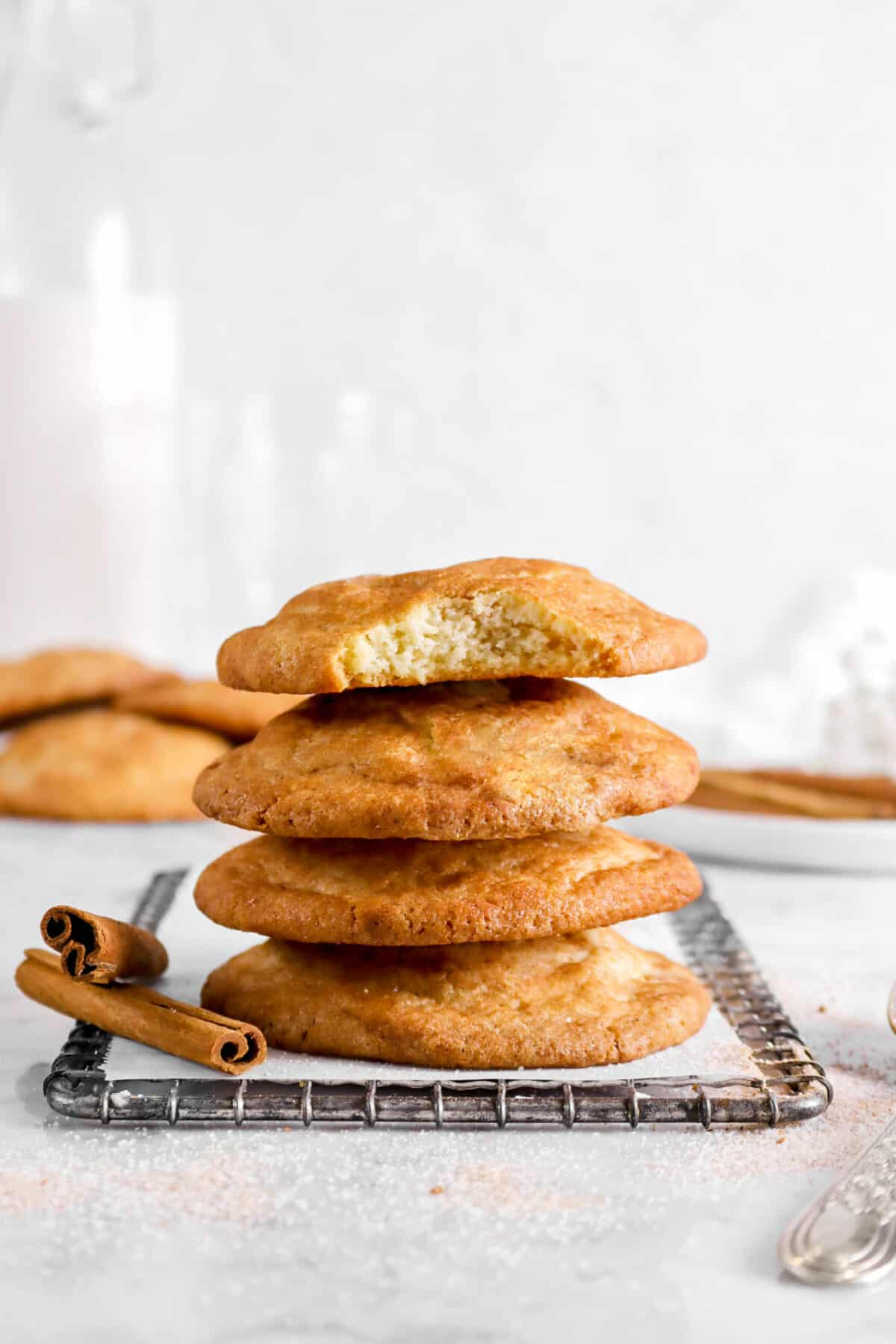four stacked cookies with a bite taken out of one on a wire cooling rack with cinnamon sticks and more cookies behind