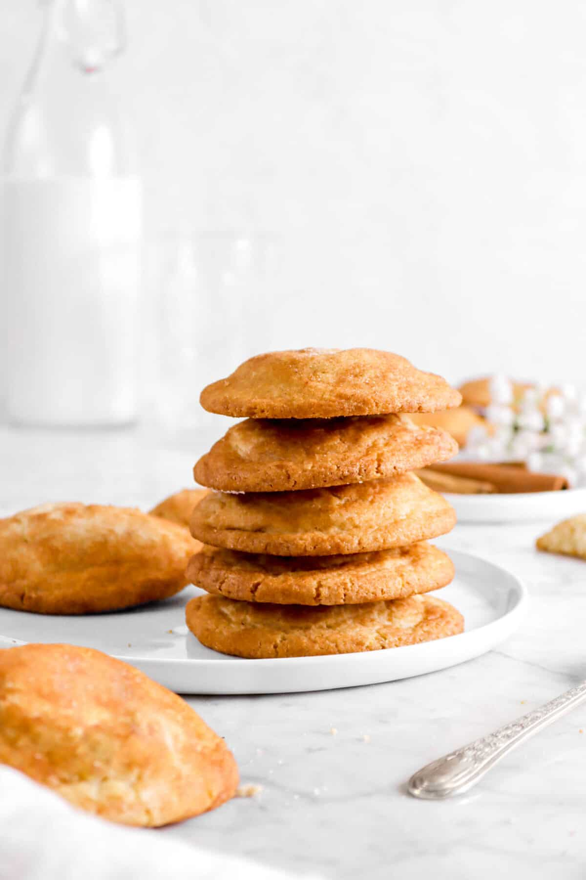 five stacked snickerdoodles on a white plate with more cookies behind and jug of milk