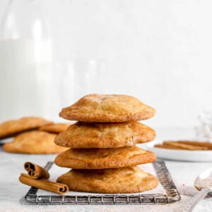 four snickerdoodle cookies stacked on wire cooling rack with two cinnamon sticks, a spoon, more cookies behind, and glass of milk