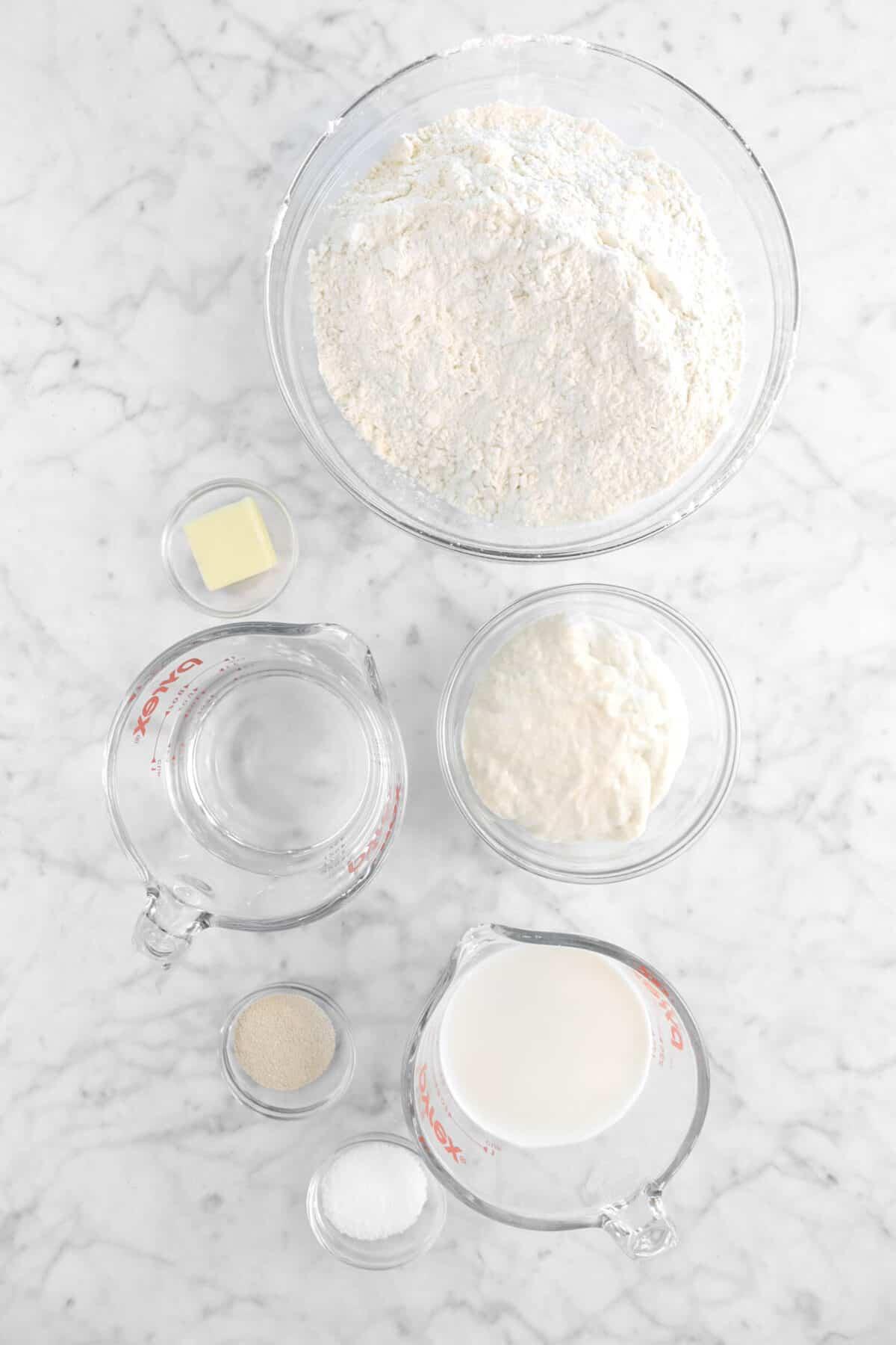 flour, butter, sourdough starter, water, milk, yeast, and salt on marble counter